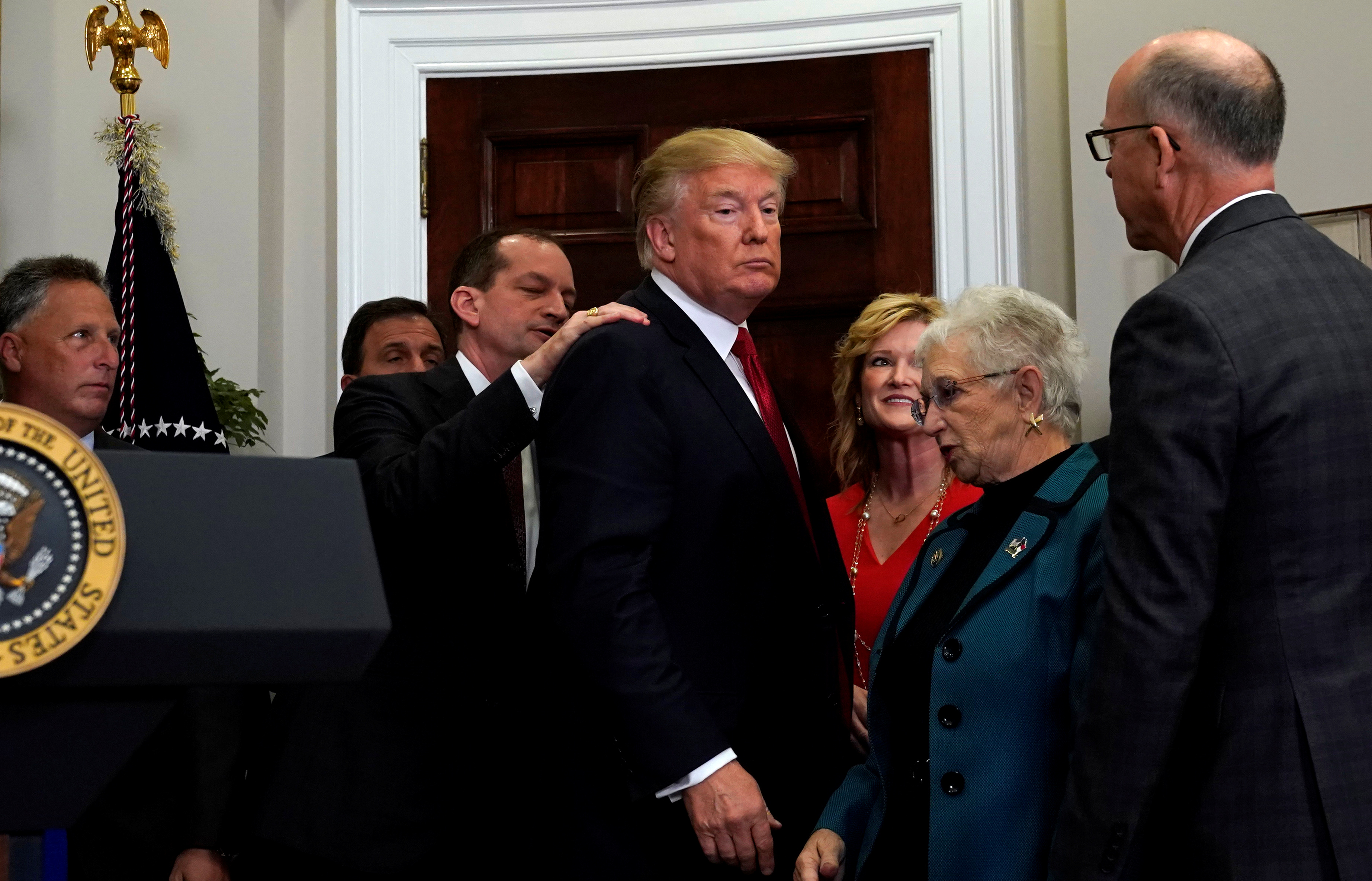 U.S. Labor Secretary Alexander Acosta puts his hand on the shoulder of U.S. President Donald Trump to prevent him from leaving the room after Trump forgot to sign an executive order on healthcare at the White House in Washington, U.S., October 12, 2017. REUTERS/Kevin Lamarque