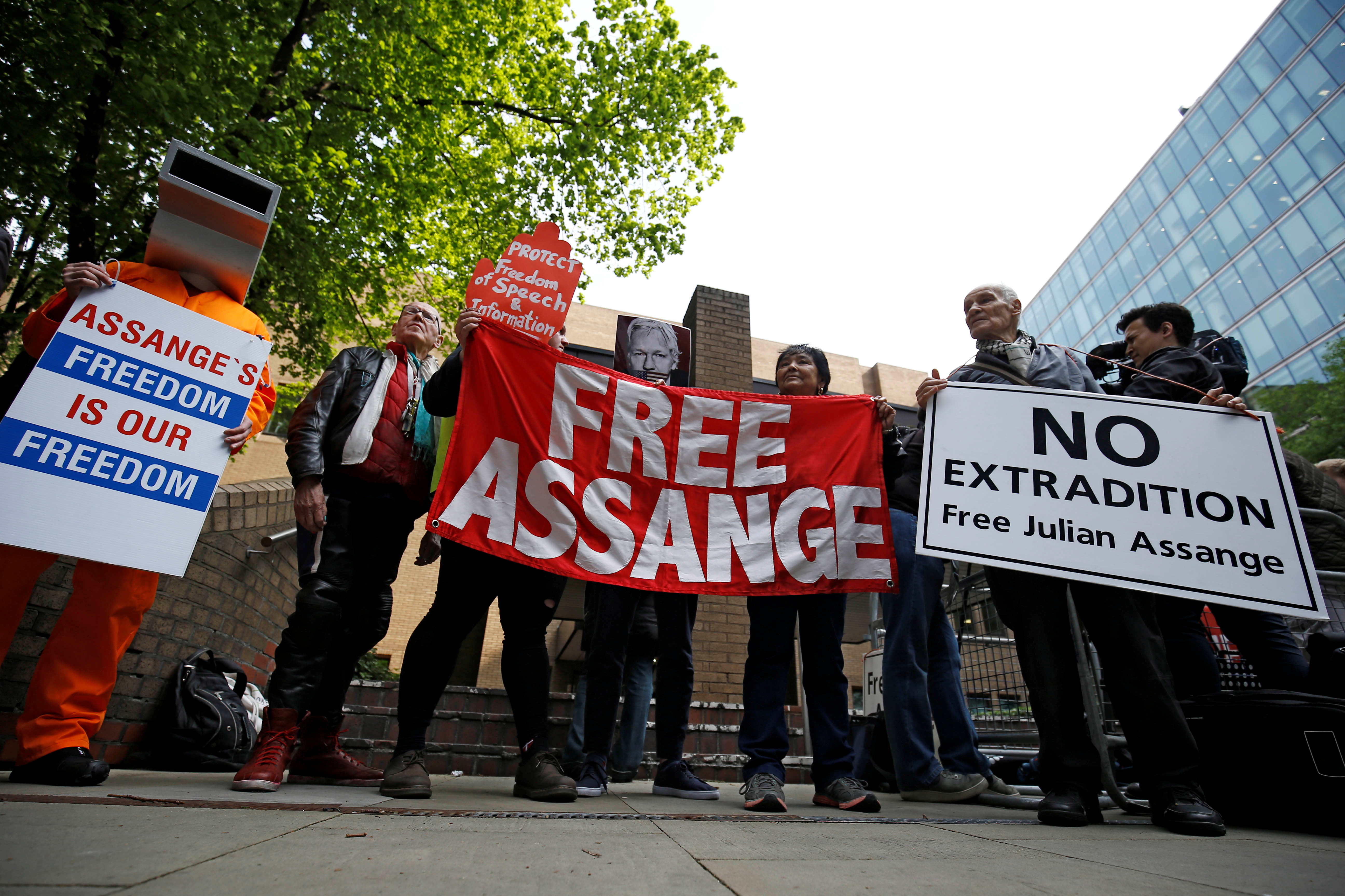 People hold signs during a protest outside Southwark Crown Court where WikiLeaks founder Julian Assange will be sentenced, in London, Britain, May 1, 2019. REUTERS/Henry Nicholls