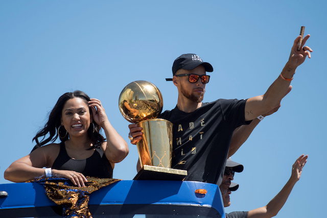 June 15, 2017; Oakland, CA, USA; Golden State Warriors guard Stephen Curry (30) waves to the crowd holding the championship trophy next to wife Ayesha Curry (left) during the Warriors 2017 championship victory parade in downtown Oakland. Mandatory Credit: Kyle Terada-USA TODAY Sports/ Reuters