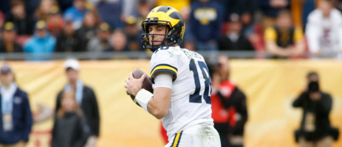 TAMPA, FL - JANUARY 1: Quarterback Brandon Peters #18 of the Michigan Wolverines looks for a receiver during the first quarter of the Outback Bowl NCAA college football game against the South Carolina Gamecocks on January 1, 2018 at Raymond James Stadium in Tampa, Florida. (Photo by Brian Blanco/Getty Images)