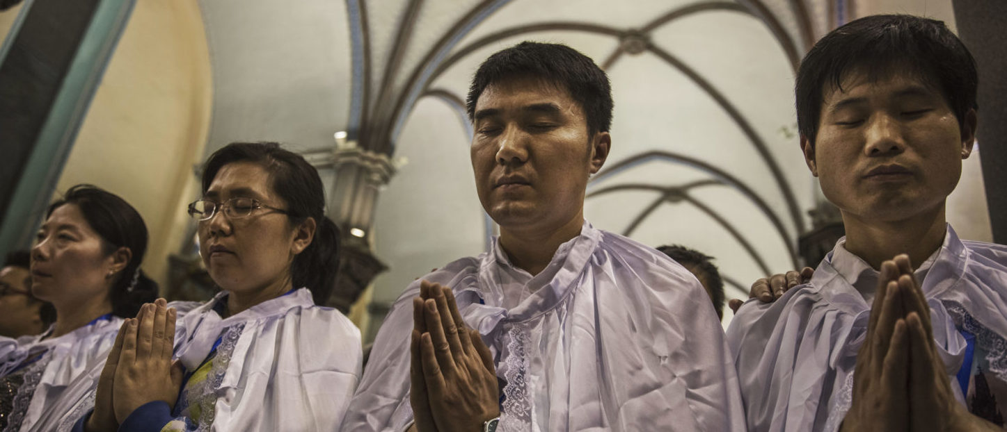 BEIJING, CHINA - APRIL 15: Newly baptized Chinese Catholic worshippers pray during a special ceremony at a mass on Holy Saturday during Easter celebrations at the government sanctioned West Beijing Catholic Church on April 15, 2017 in Beijing, China. China, an officially atheist country, places a number of restrictions on Christians, allowing legal practice of the faith only at state-approved churches. The policy has driven an increasing number of Christians and Christian converts 'underground' to congregations in private homes and other venues. While the size of the religious community is difficult to measure, studies estimate there are more than 80 million Christians inside China; some studies support the possibility it could become the most Christian nation in the world in the coming years. Officially there have been no relations between China and the Vatican since the country's modern founding in 1949 though in recent years there have been signs of warming relations between Chinese president Xi Jinping and Pope Francis that could possibly allow greater religious freedom in the future. At present, the split means approved Chinese Christians worship within a state-sanctioned Church known as the Patriotic Association which regards the Communist Party as its leader, not the Pope in Rome. (Photo by Kevin Frayer/Getty Images)