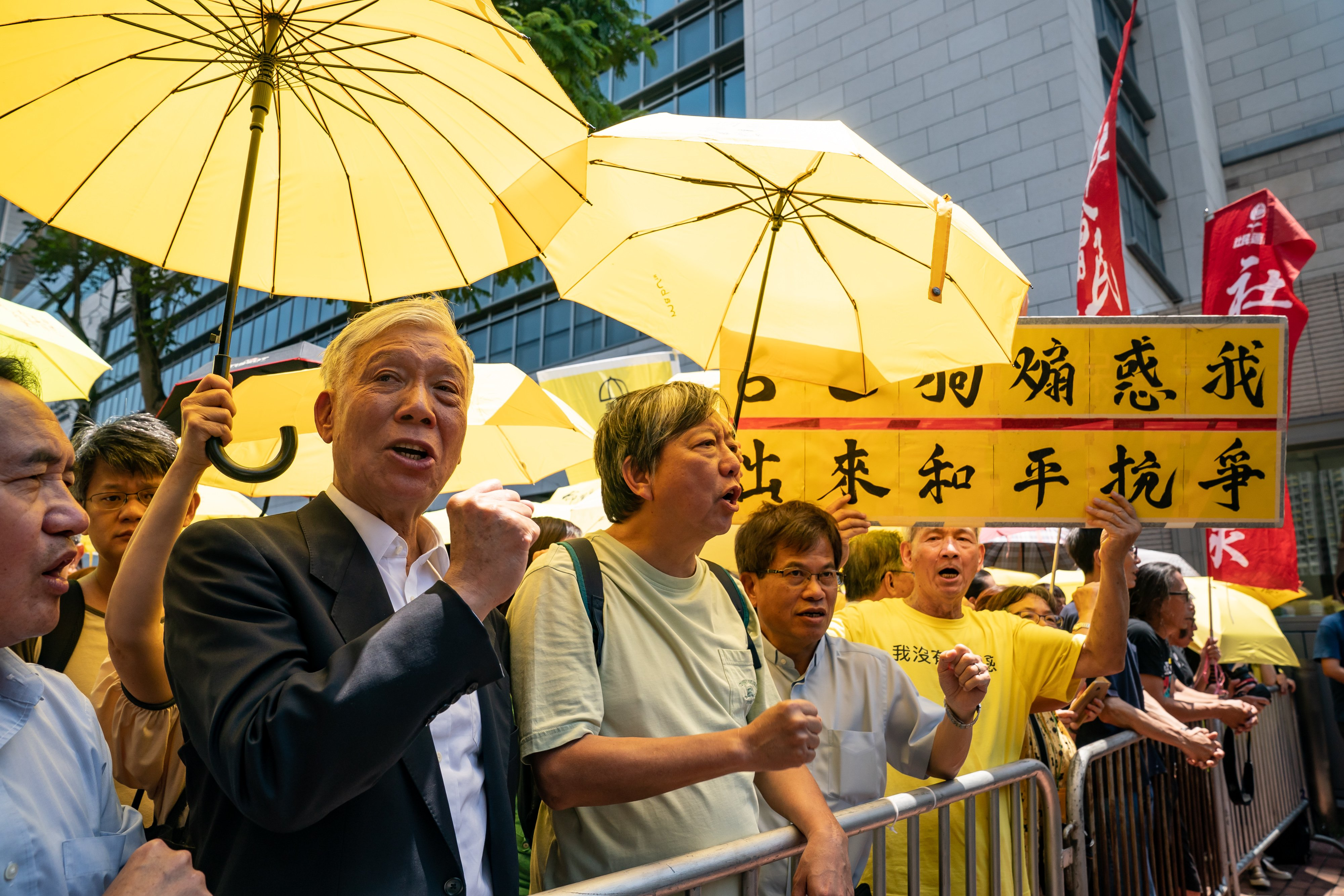 HONG KONG, APRIL 24: Occupy co-founder Reverend Chu Yiu-ming and pro-democracy activist Lee Cheuk-yan shout slogans as they wait for the prison car outside of the West Kowloon Courts Building after the sentencing of the 'Occupy 9' on April 24, 2018 in Hong Kong, Hong Kong. (Photo by Anthony Kwan/Getty Images)