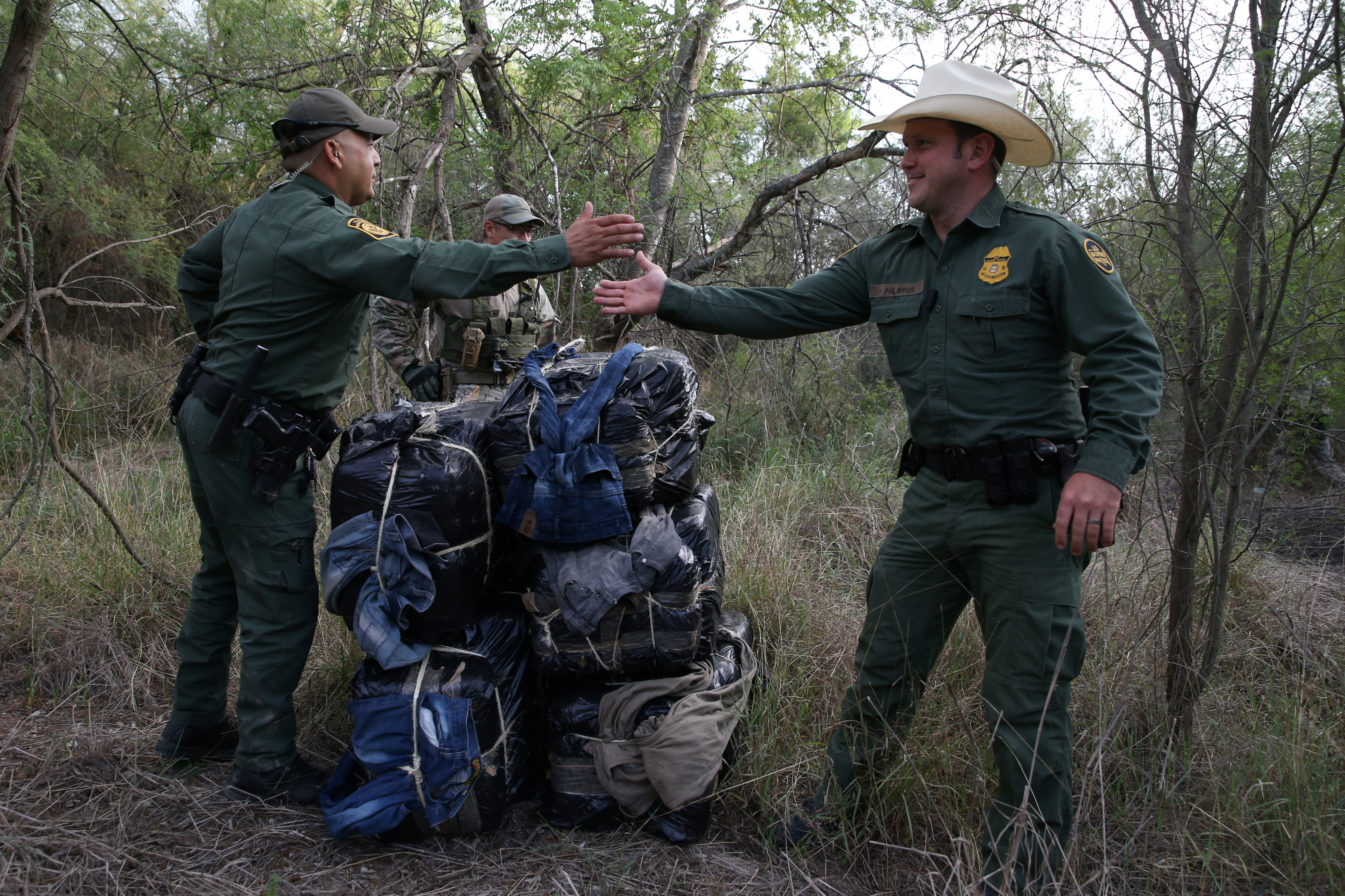 Border patrol agents congratulate each other after seizing 297 pounds of marijuana following a drug bust by the Mexico-U.S. border near McAllen