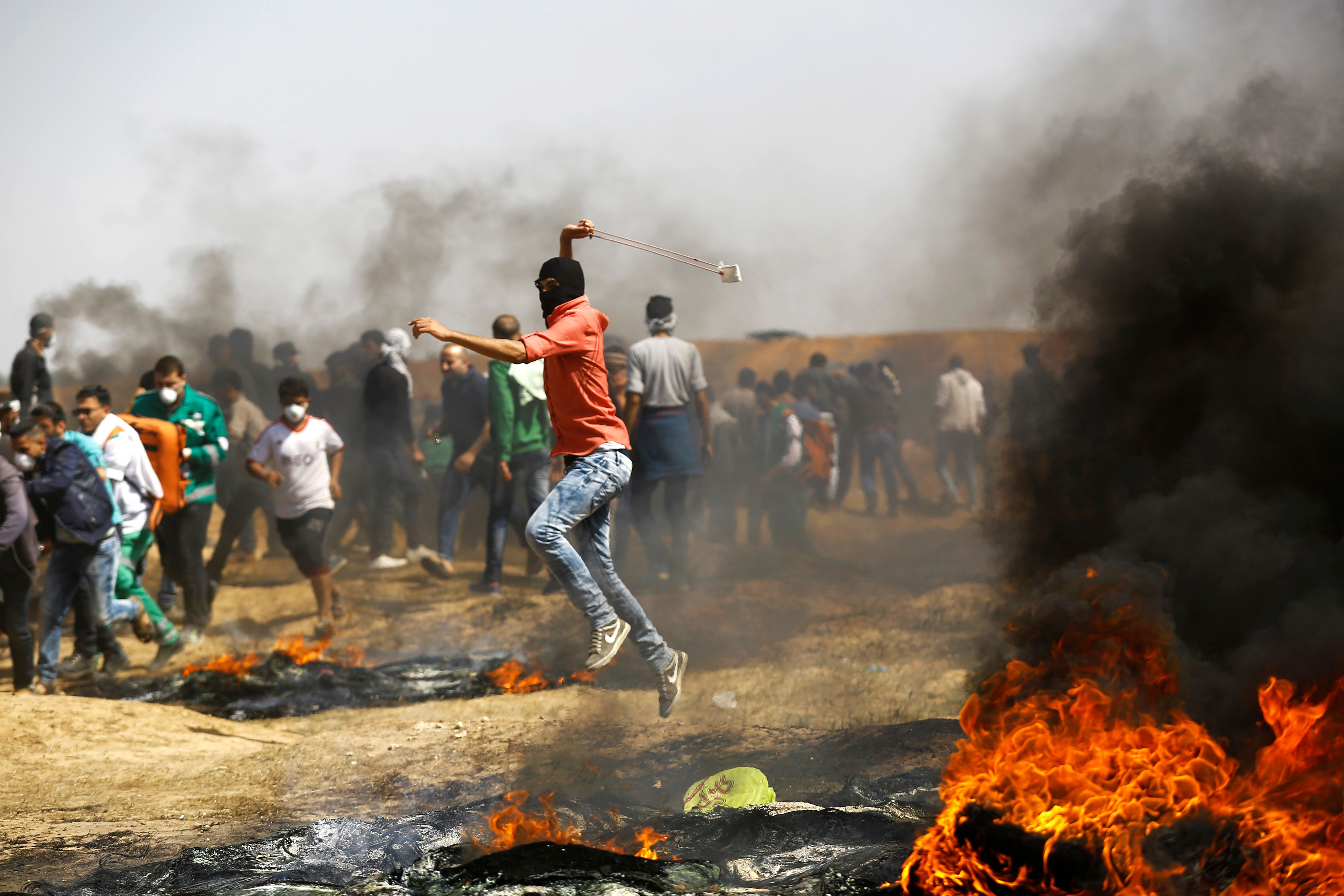 TOPSHOT - A Palestinian demonstrator uses a slingshot to throw stones during clashes with Israeli security forces following a protest on the Israel-Gaza border east of the Jabalia refugee camp in the northern Gaza Strip on April 6, 2018. (MOHAMMED ABED/AFP/Getty Images)