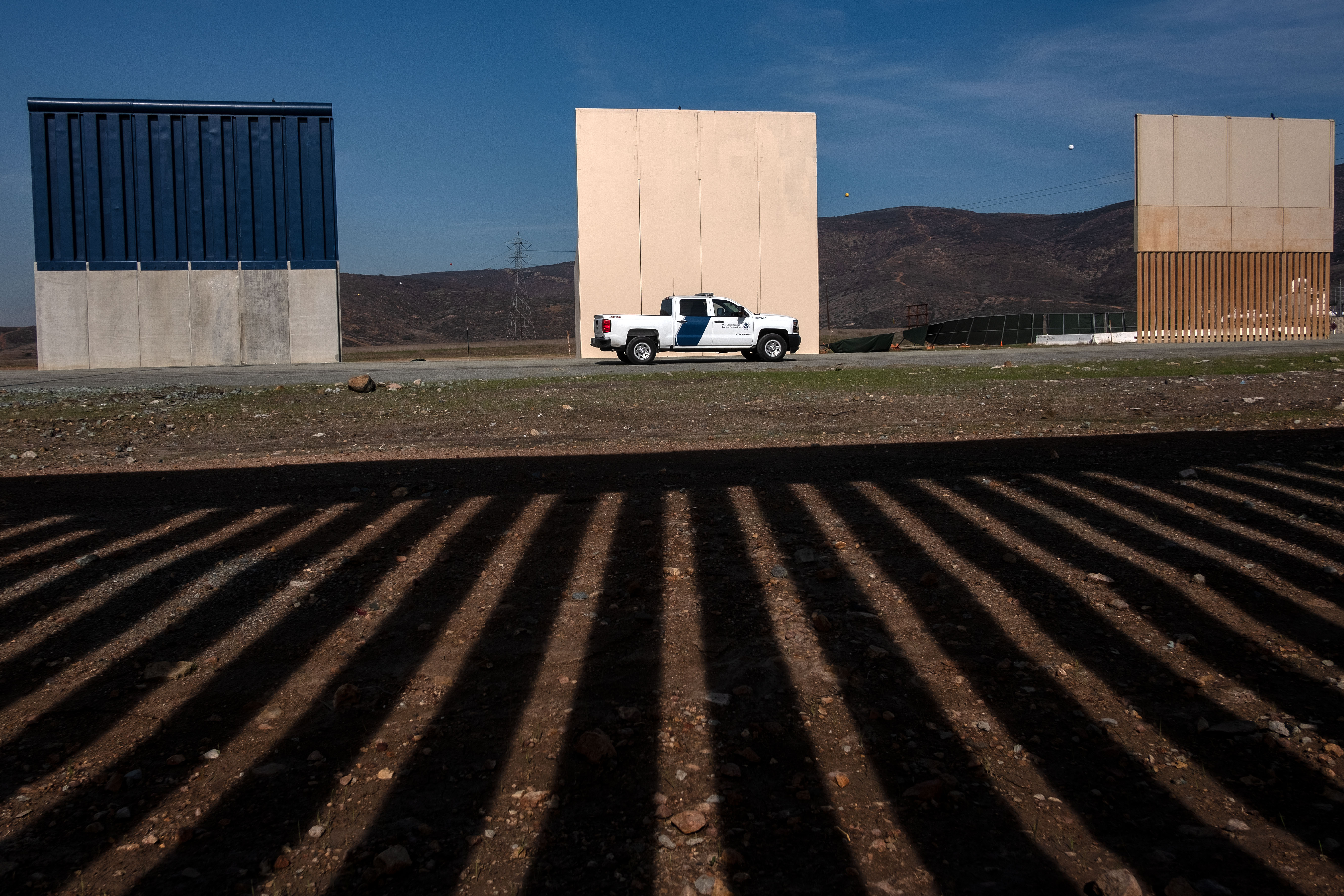 A Customs and Border protection vehicle passes by US President Donald Trump's wall prototypes, as seen from behind the Mexico-US border fence in Tijuana, Baja California state, Mexico on December 12, 2018. - As thousands of Central American migrants, mostly Hondurans, have trekked for over a month in the hopes of reaching the United States, President Donald Trump told Democratic leaders at the White House on Tuesday that he will shut down the US government because they refuse to approve billions of dollars in funding for his controversial Mexico border wall. (Photo by GUILLERMO ARIAS/AFP/Getty Images)
