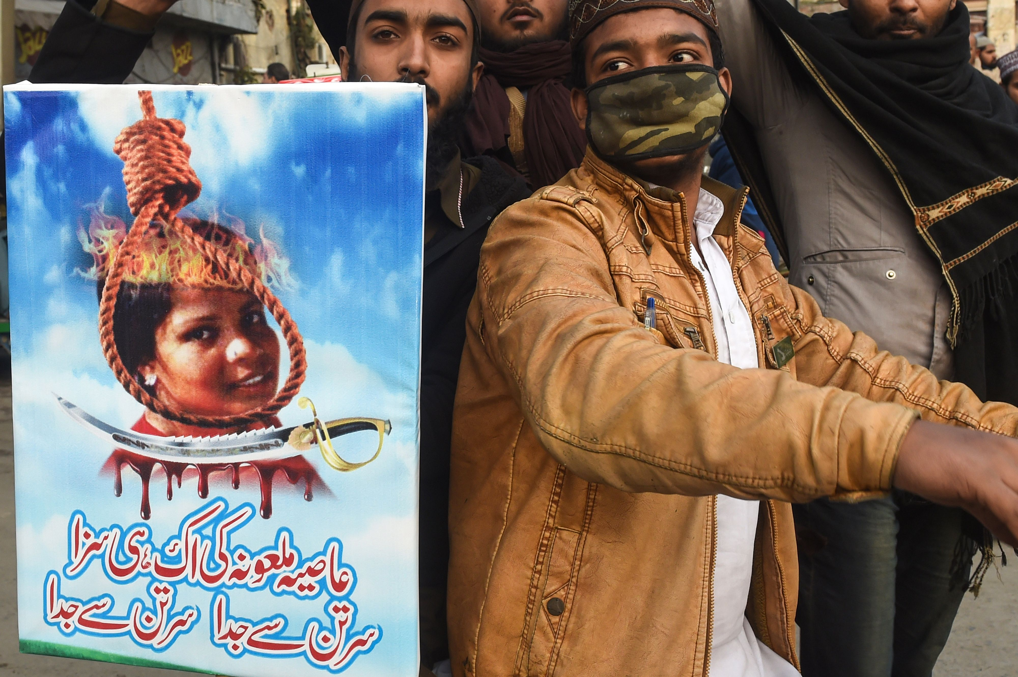 Pakistani Islamists hold a poster displaying the portrait of Asia Bibi, a Christian Pakistani woman accused of blasphemy, during a protest against the Supreme Court decision on Bibi's case in Lahore on February 1, 2019. (Photo by ARIF ALI/AFP/Getty Images)