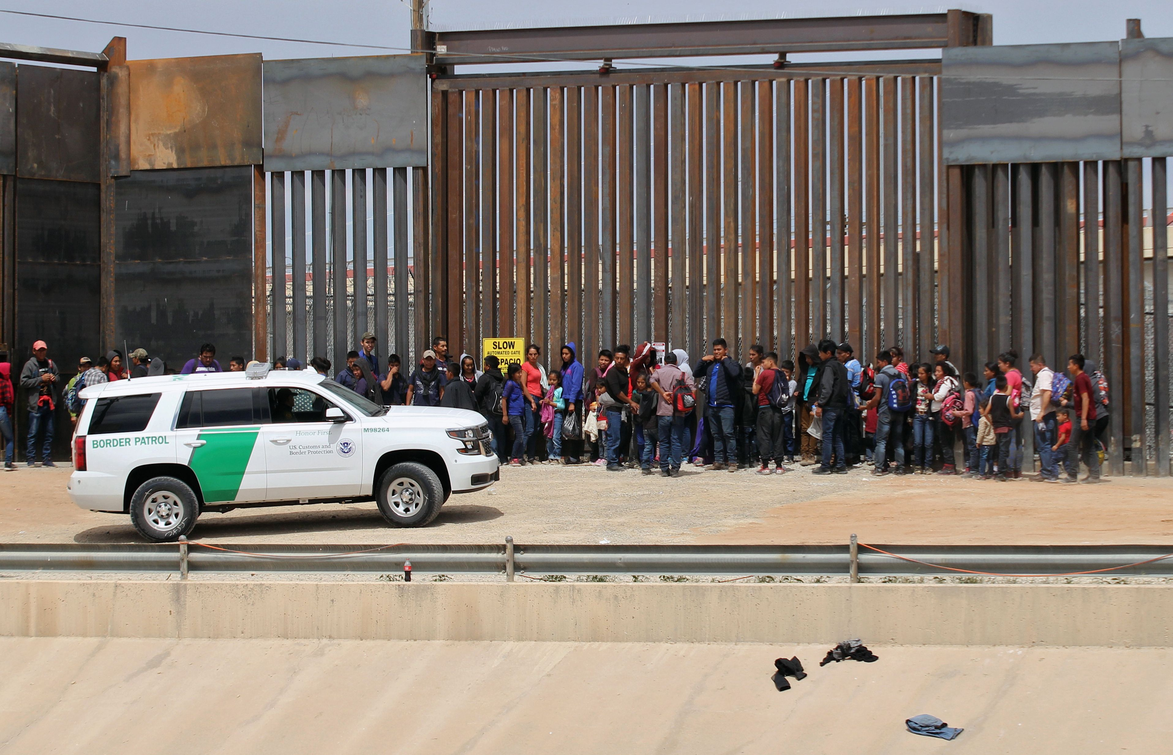 TOPSHOT - Central American migrants are detained by US Customs and Border Patrol agents at the border wall in Ciudad Juarez, Chihuahua state, Mexico, on May 7, 2019. (Photo by HERIKA MARTINEZ/AFP/Getty Images)