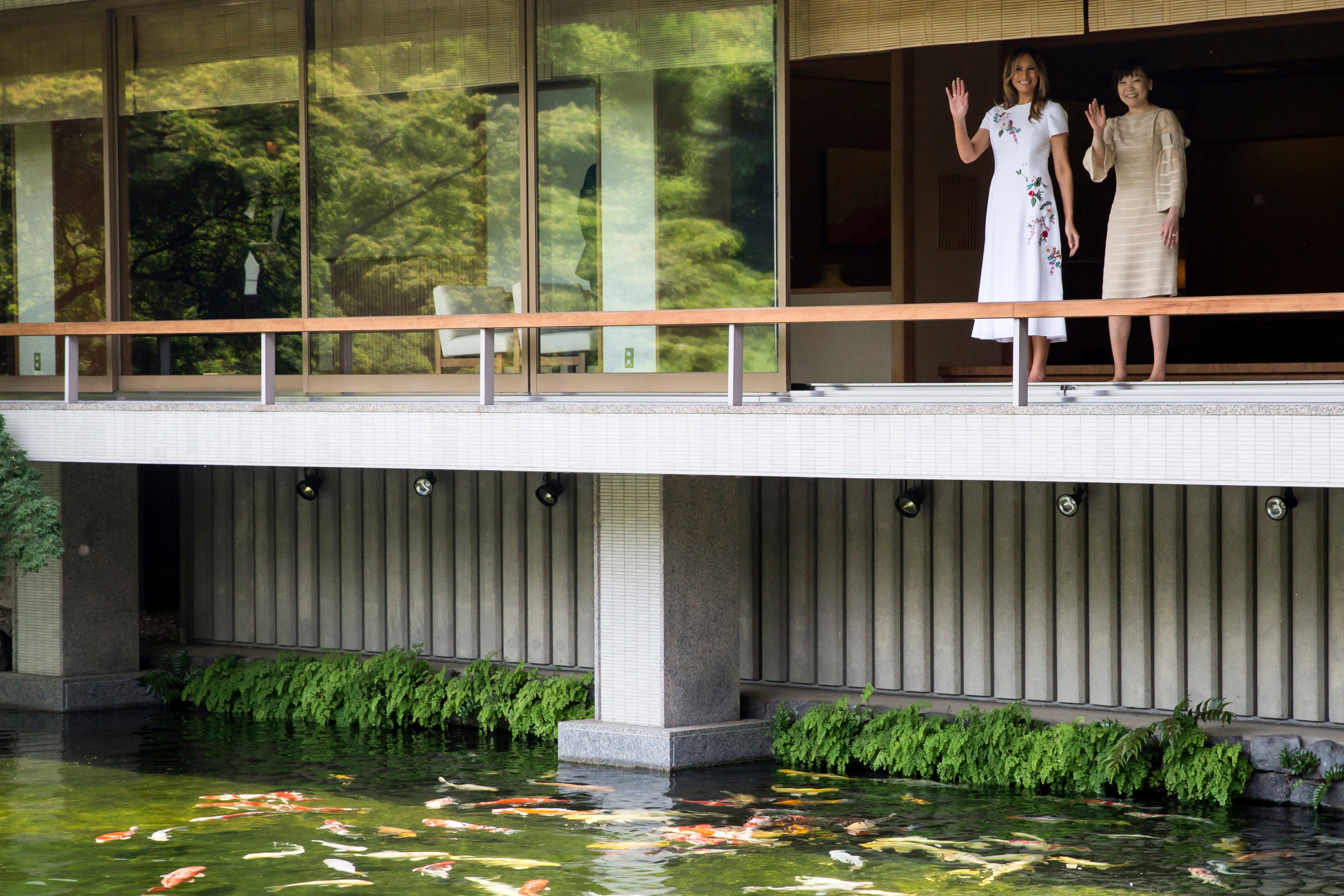 US First Lady Melania Trump (L) and Akie Abe, wife of Japanese Prime Minister Shinzo Abe (R) wave after looking at koi carps in a pond at the Japanese style annex inside the State Guest House in Tokyo on May 27, 2019. (Photo by TOMOHIRO OHSUMI/AFP/Getty Images)