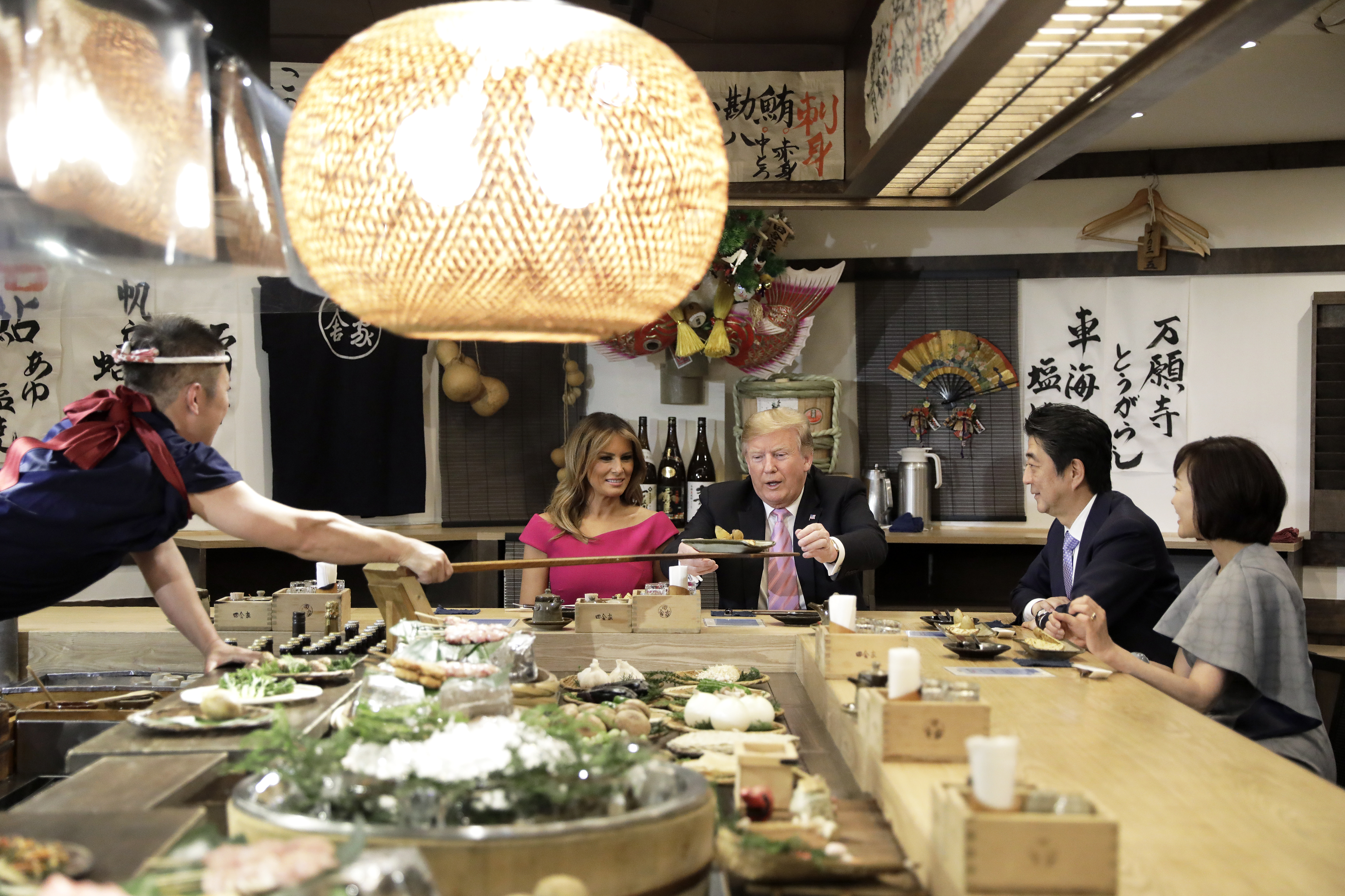 TOKYO, JAPAN - MAY 26: U.S. President Donald Trump, center, is served a baked potato with butter while sitting at a counter with First Lady Melania Trump, second left, Shinzo Abe, Japan's Prime Minister, second right, and Akie Abe, wife of Shinzo Abe, right, during a dinner at the Inakaya restaurant in the Roppongi district on May 26, 2019 in Tokyo, Japan. (Photo by Kiyoshi Ota - Pool/Getty Images)