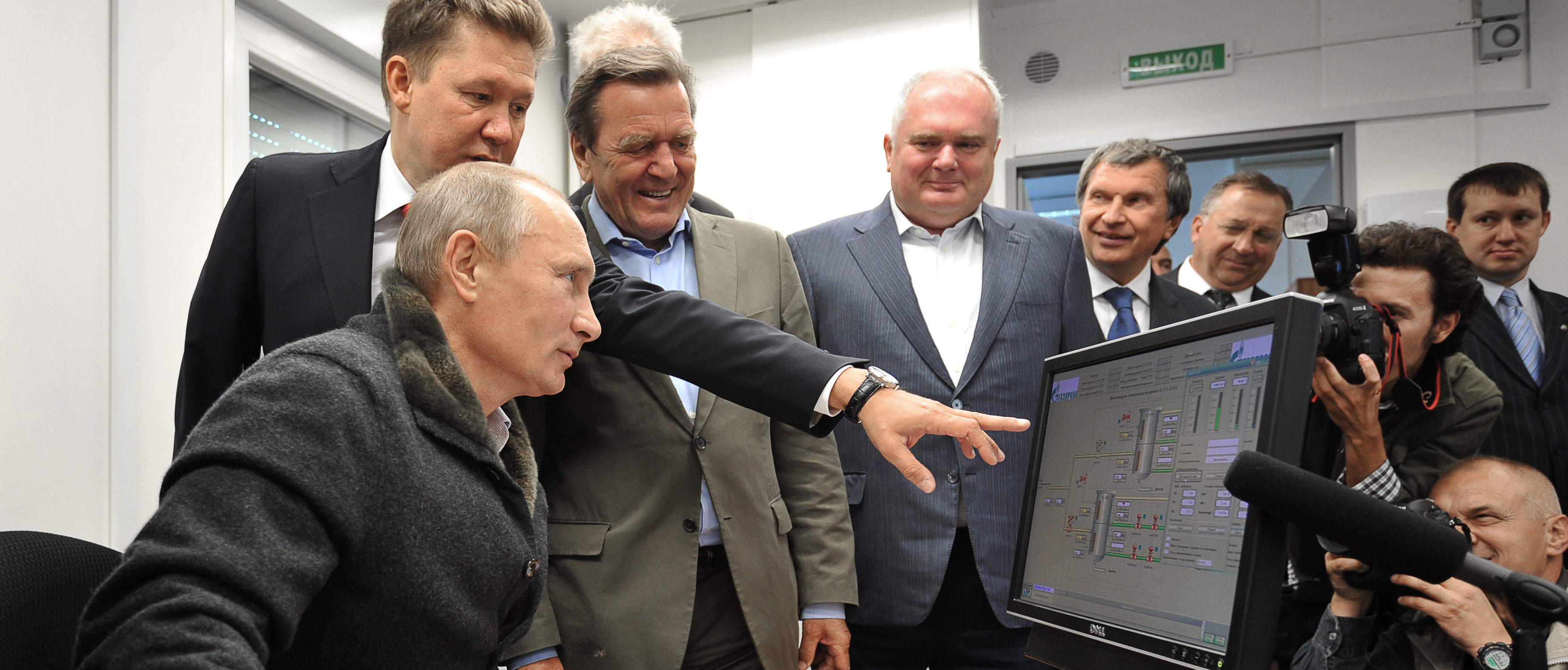 """Russian Prime Minister Vladimir Putin (L),Gazprom Chief Executive Officer Alexei Miller (2nd L) and former German chancellor Gerhard Schroeder (3rd L) look at a screen as they attend the inauguration of the Nord Stream Project information mount at the gas compressor station """"Portovaya"""" outside Vyborg, September 6, 2011. ALEXEY NIKOLSKY/AFP/Getty Images)"""