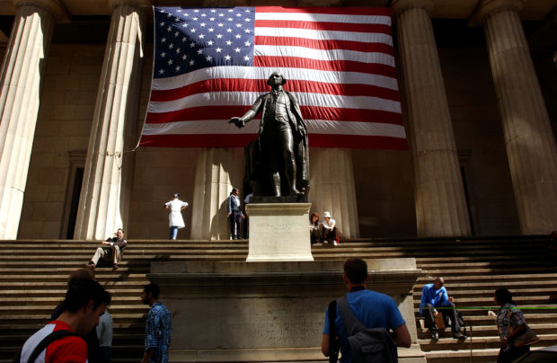 Pedestrians walk around the George Washington statue in front of Federal Hall September 5, 2002 in New York City. (Spencer Platt/Getty Images)