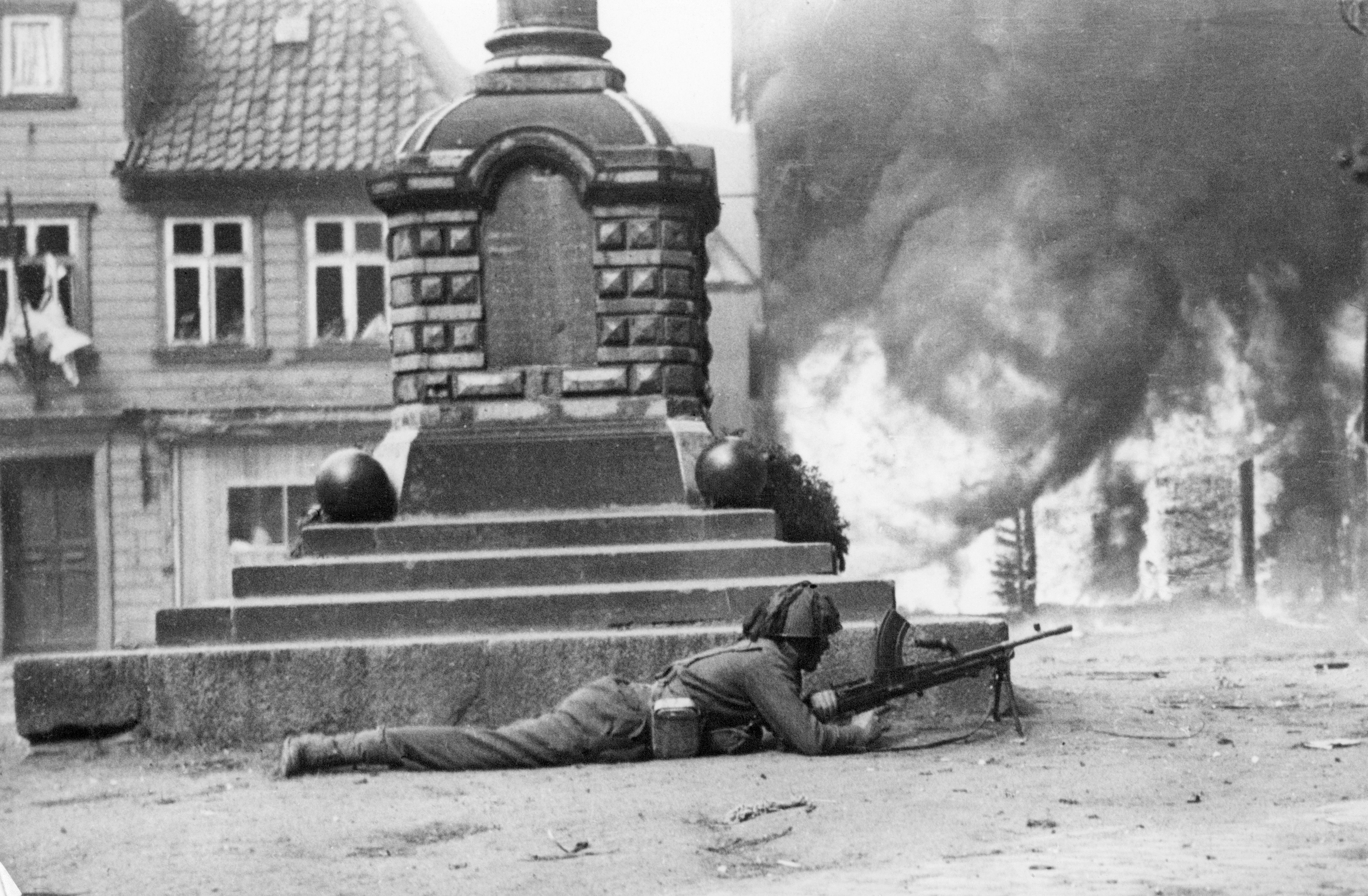 An Allied soldier with a machine gun surveys the crossroads of a partially occupied German village in April 1945 at the end of World War II. (Photo by AFP/Getty Images)