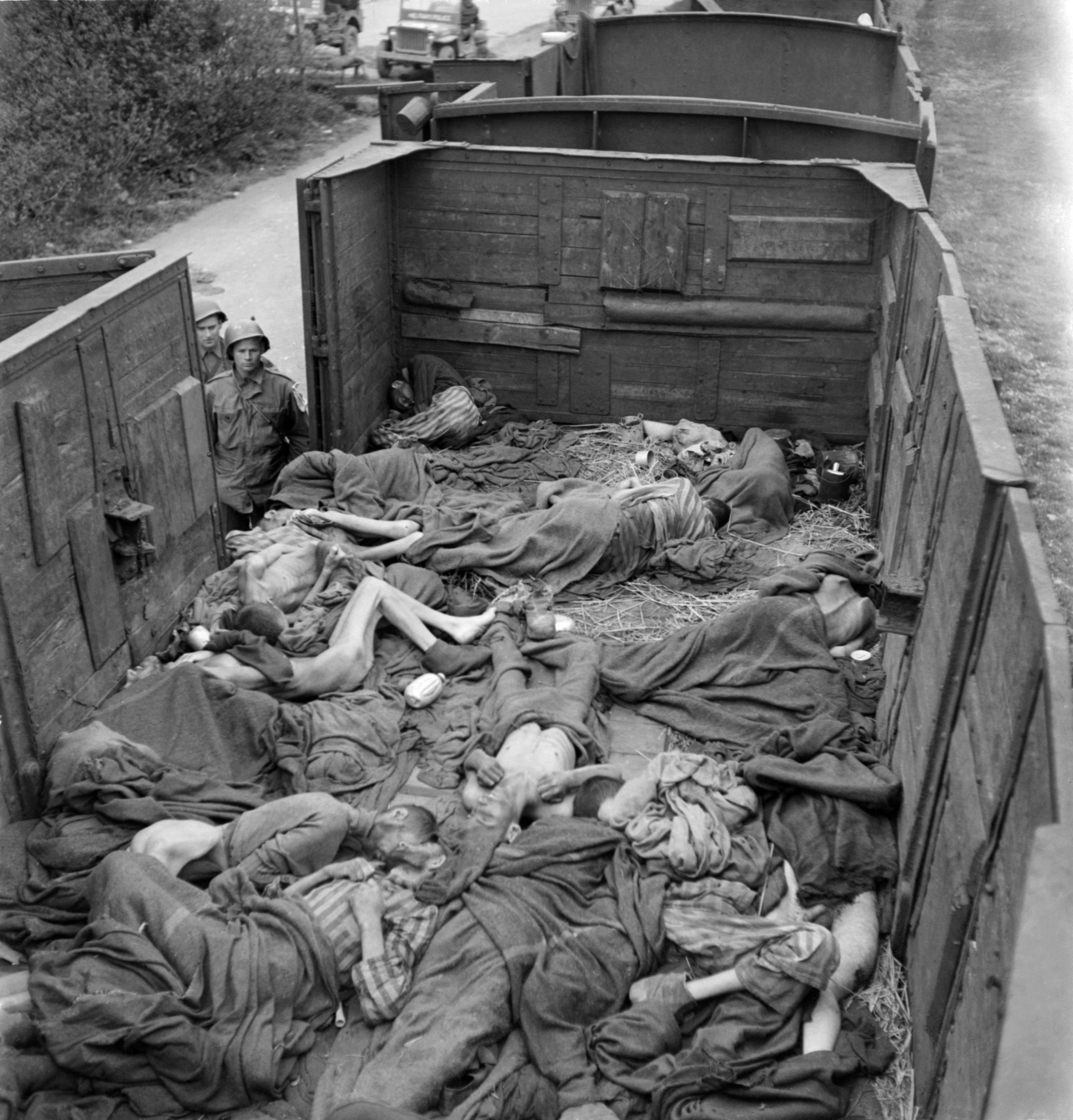 US soldiers look at the pile of prisoner's dead bodies in a train near Dachau concentration camp in late April or early May 1945, after the camp was liberated by the US army on April 29, 1945. (Photo by ERIC SCHWAB/AFP/Getty Images)