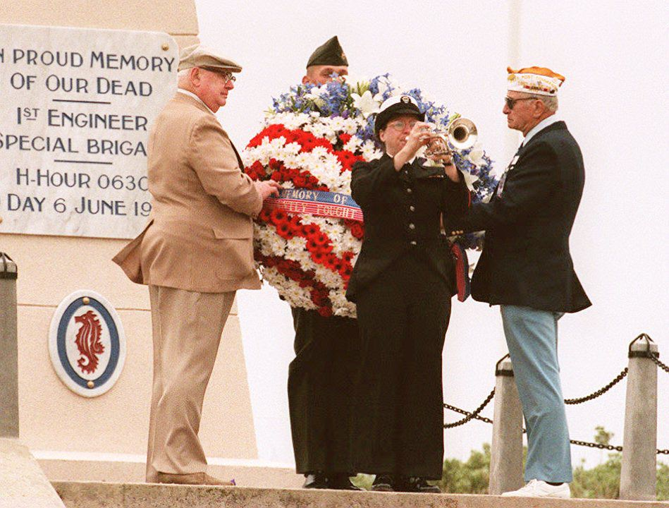 "UTAH BEACH, FRANCE: As a sailor plays ""Taps,"" US veterans of the 06 June 1944 D-Day invasion lay a wreath 06 June 1994 in front of a monument at Utah Beach during commemoration ceremonies of the 50th anniversary of the landing. (Photo by PASCAL GUYOT/AFP/Getty Images)"