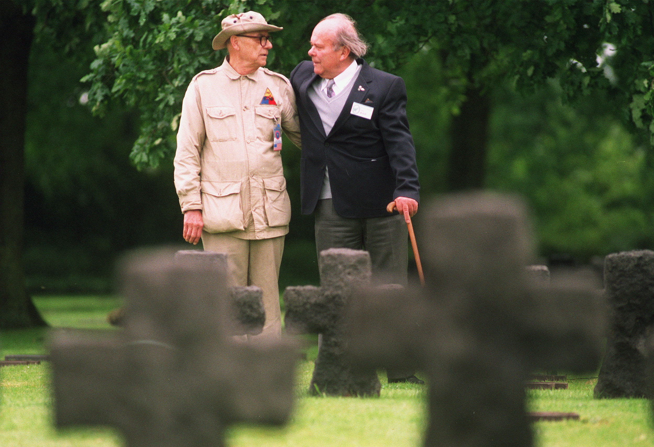 LA CAMBE, FRANCE: German veteran Peter Brack (R) from Cologne and US veteran Jack Boardman from Chicago chat in the German cemetery of La Cambe 04 June 1994 during a meeting between veterans of both countries. (Photo by JOEL SAGET/AFP/Getty Images)