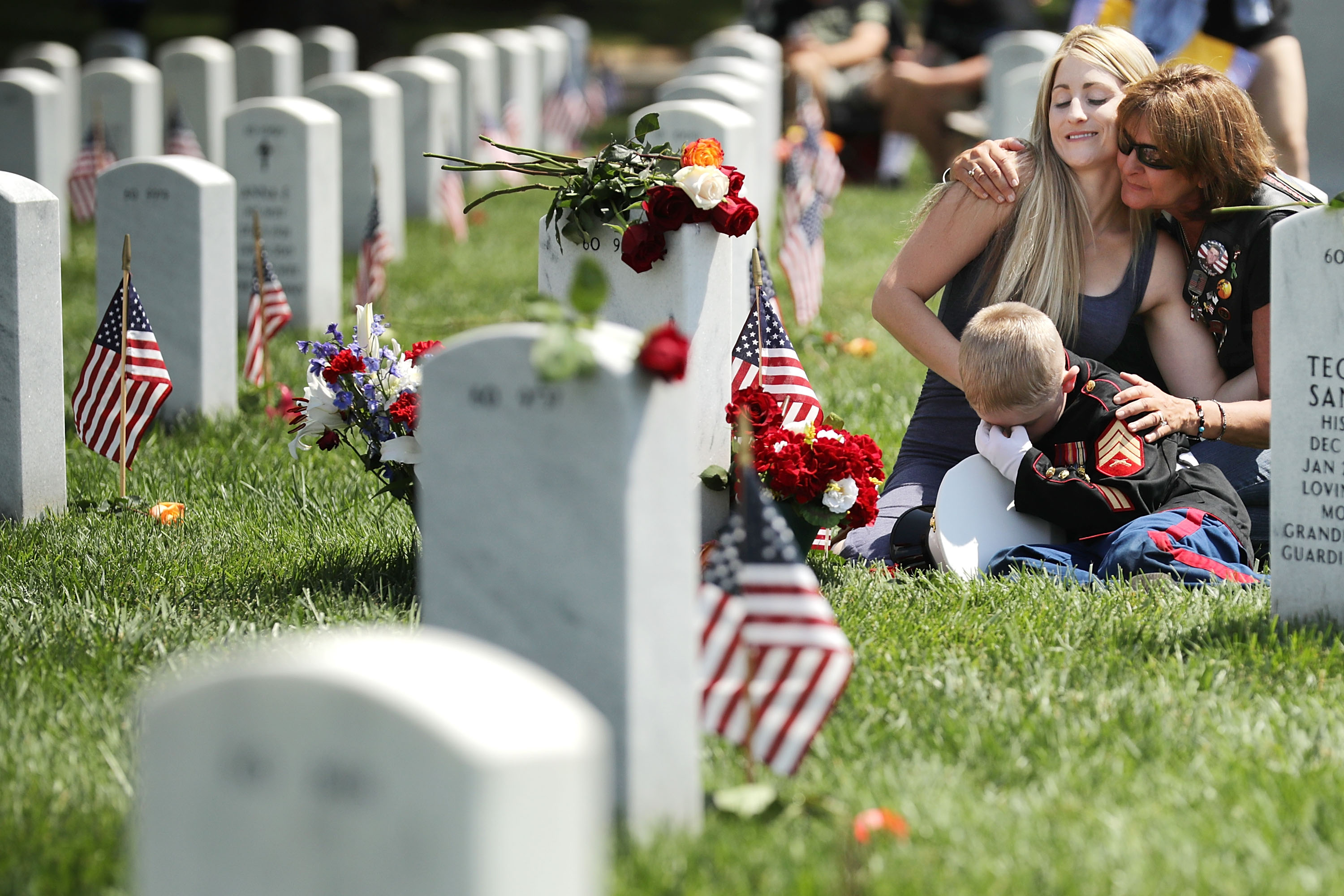 ARLINGTON, VA - MAY 29: Brittany Jacobs (L) of Hertford, North Carolina, and her son, Christian Jacobs, 6, are embraced by a friend while sitting next to the grave of Brittany's husband, U.S. Marine Corps Sgt. Chris Jacobs, in Section 60 at Arlington National Cemetery on Memorial Day May 29, 2017 in Arlington, Virginia. Part of the 3rd Assault Amphibian Battalion, 1st Marine Division, Sgt. Jacobs served in Aghanistan and Iraq and was killed during a training exercise in California in 2011. (Photo by Chip Somodevilla/Getty Images)