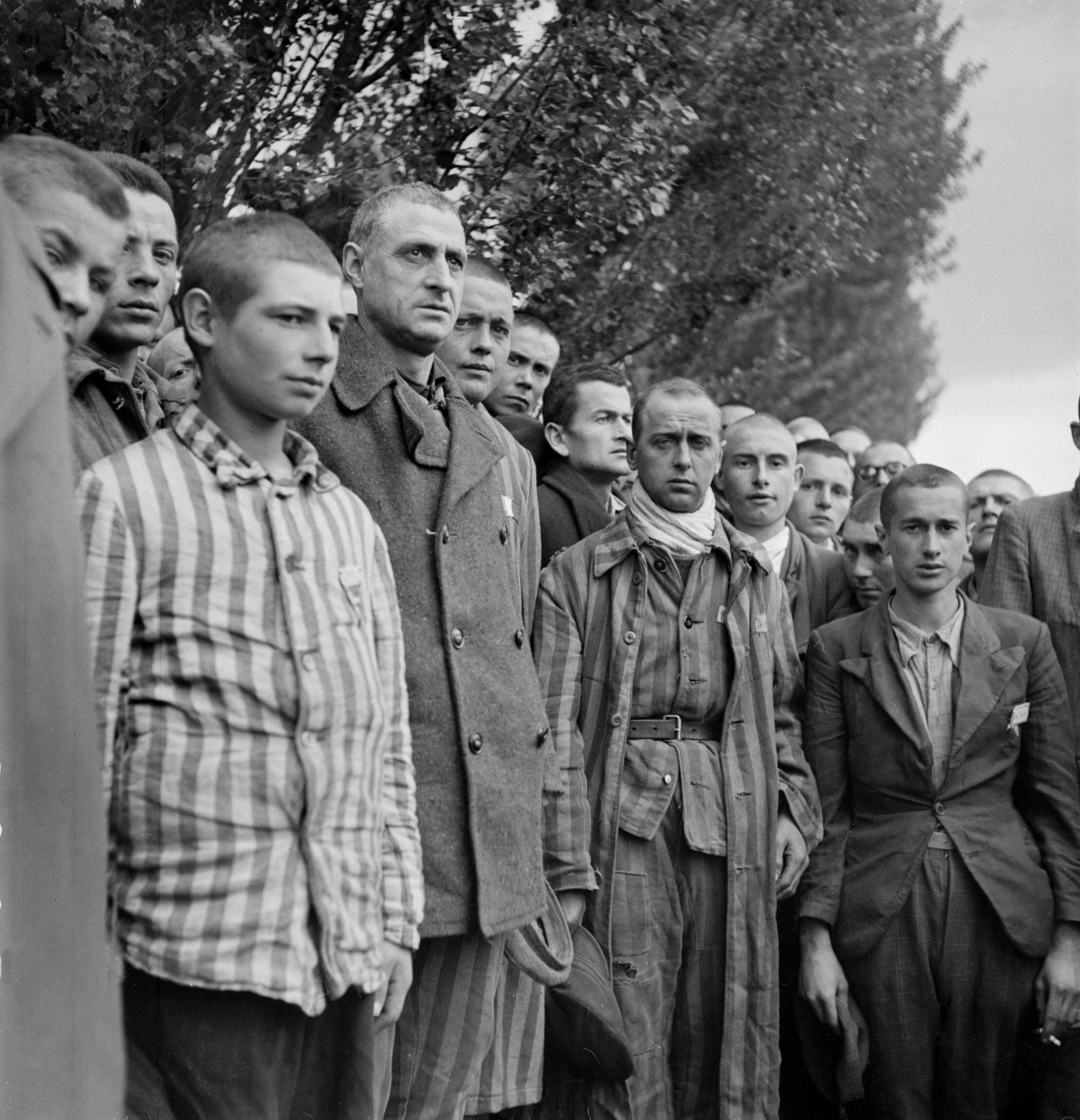 "French prisoners sing their national anthem, ""La Marseillaise"", upon the liberation of the Nazi concentration camp of Dachau, near Munich, by Allied troops at the end of April 1945. (Photo by ERIC SCHWAB/AFP/Getty Images)"