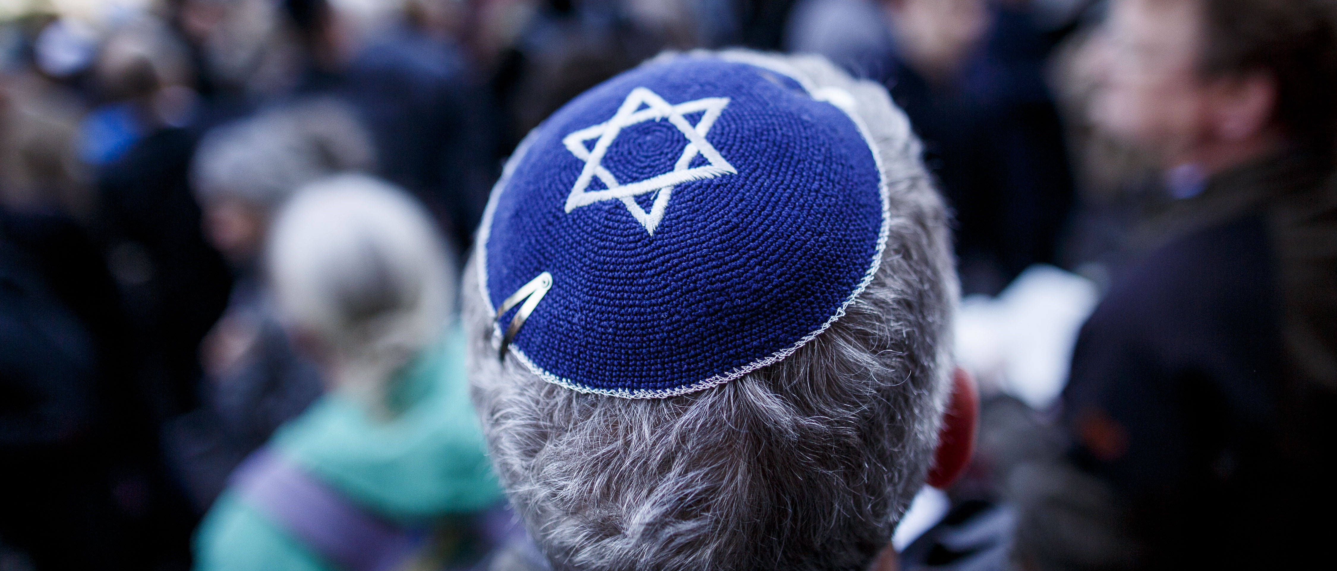 """BERLIN, GERMANY - APRIL 25: A participant wears a kippah during a """"wear a kippah"""" gathering to protest against anti-Semitism in front of the Jewish Community House on April 25, 2018 in Berlin, Germany. The Jewish community made a public appeal for Jews and non-Jews to attend the event and wear a kippah as a show of solidarity. The effort was sparked by a recent incident in Berlin in which a Syrian Palestinian man berated and struck with his belt a man wearing a kippah. The kippah-wearer was not Jewish, but an Israeli Arab who wore the kippah curious what reaction he might receive while walking in Berlin. In 2017 Germany reportedly recorded 1453 criminal offenses related to anti-Semitism, of which 94 percent were attributed to German citizens. (Photo by Carsten Koall/Getty Images)"""