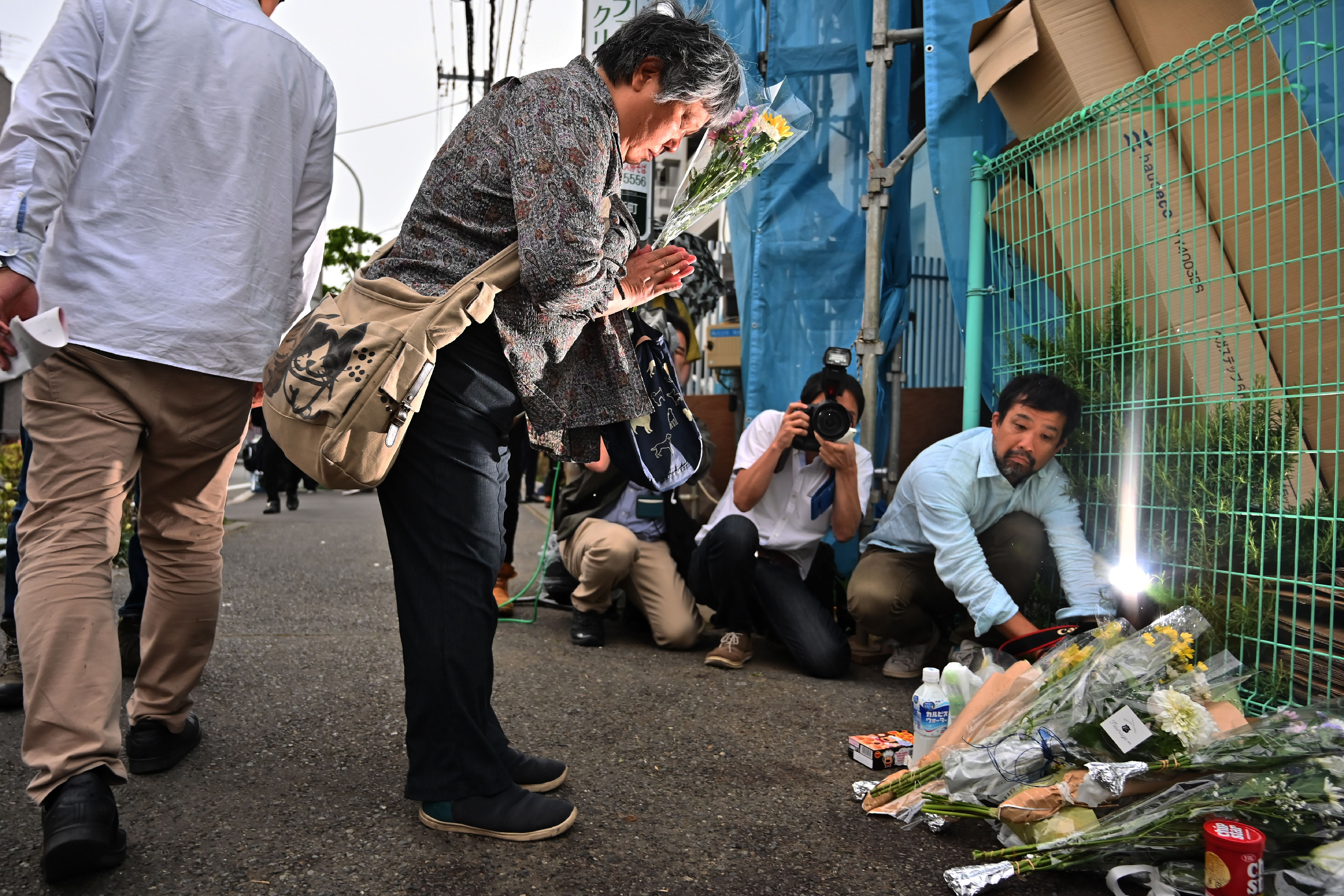 A woman pays her respects next to flower tributes at the crime scene where a man stabbed 19 people, including children, in Kawasaki on May 28, 2019. - A knife-wielding attacker killed a 12-year-old schoolgirl and a man before stabbing himself to death in a rampage outside Tokyo that also injured more than a dozen, including several children. (Photo by CHARLY TRIBALLEAU/AFP/Getty Images)