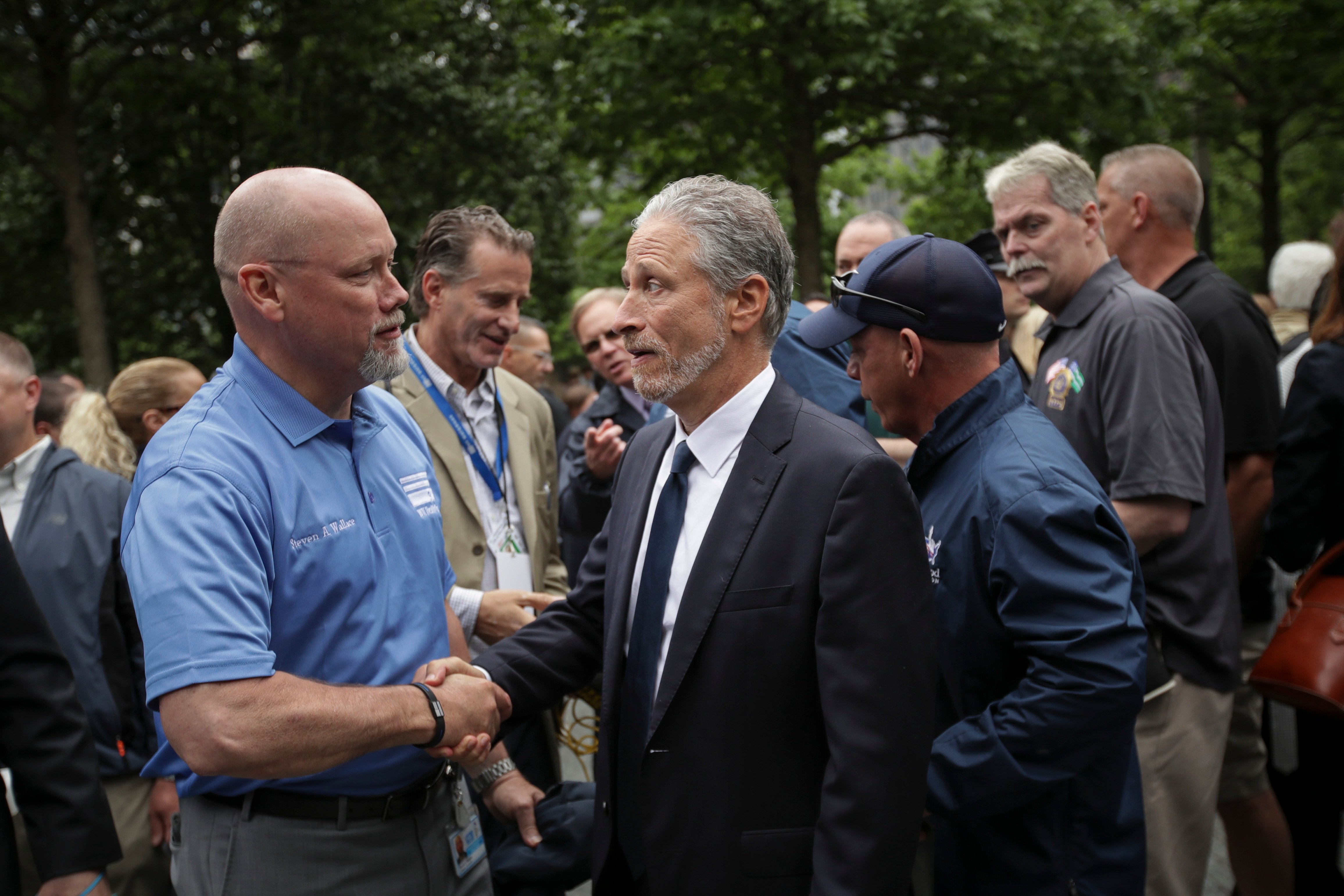 NEW YORK, NY - MAY 30: Comedian and 9/11 healthcare advocate Jon Stewart greets attendees at the dedication ceremony for the new 9/11 Memorial Glade at the National September 11 Memorial, May 30, 2019 in New York City. The 9/11 Memorial Glade honors the first responders who are sick or have died from exposure to toxins in the aftermath of the attacks and recovery efforts. The signature piece of the memorial are six stone monoliths that are inlaid with World Trade Center steel. (Photo by Drew Angerer/Getty Images)