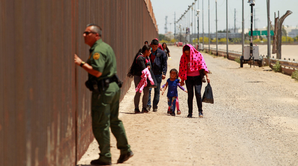 A group of Central American migrants walks next to the U.S.-Mexico border fence after they crossed the borderline while a Border Patrol agent looks through the fence in El Paso, Texas, U.S May 15, 2019. REUTERS/Jose Luis Gonzalez