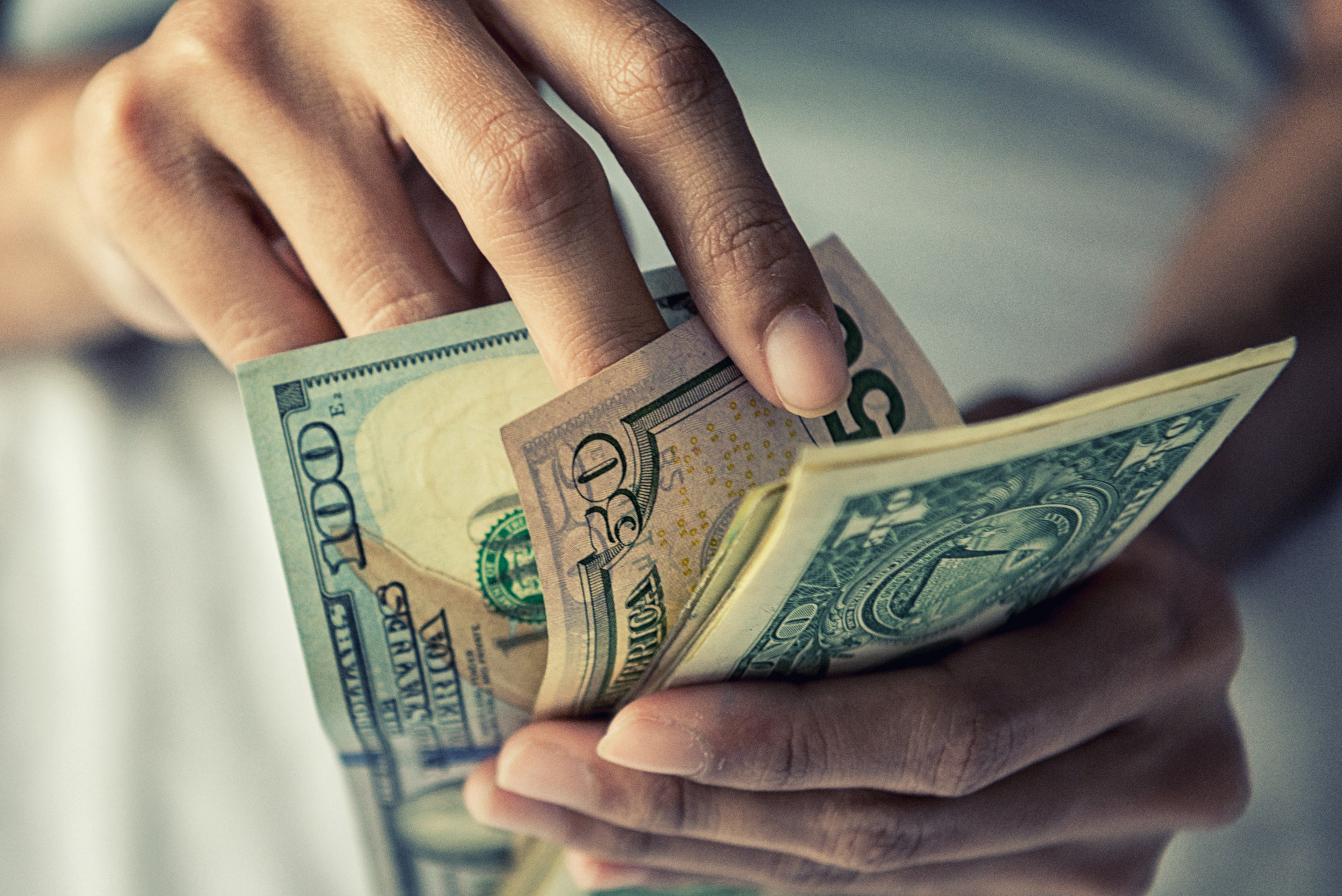 Close-up Hands counting money American dollars. Shutterstock