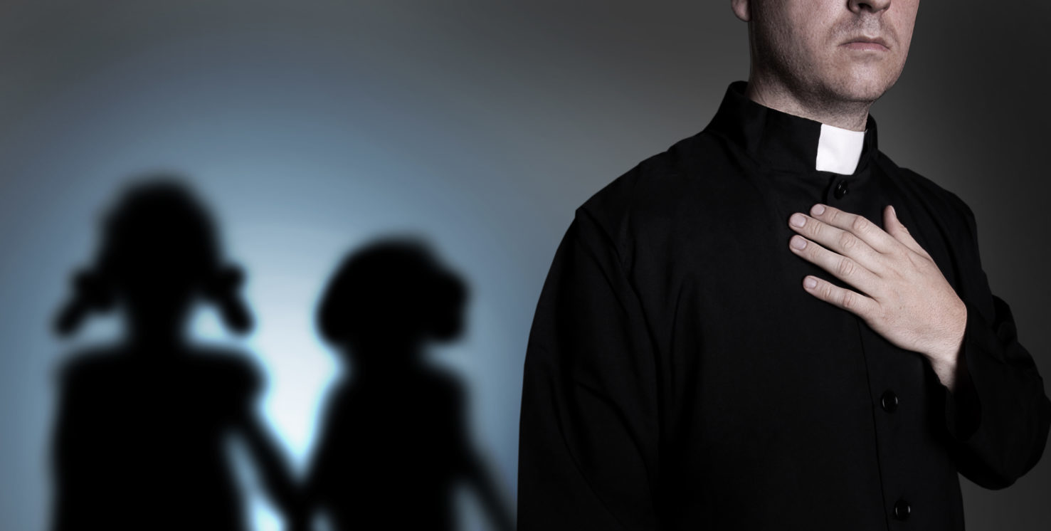 A Catholic priest with children silhouetted behind him (Shutterstock/ambrozinio)