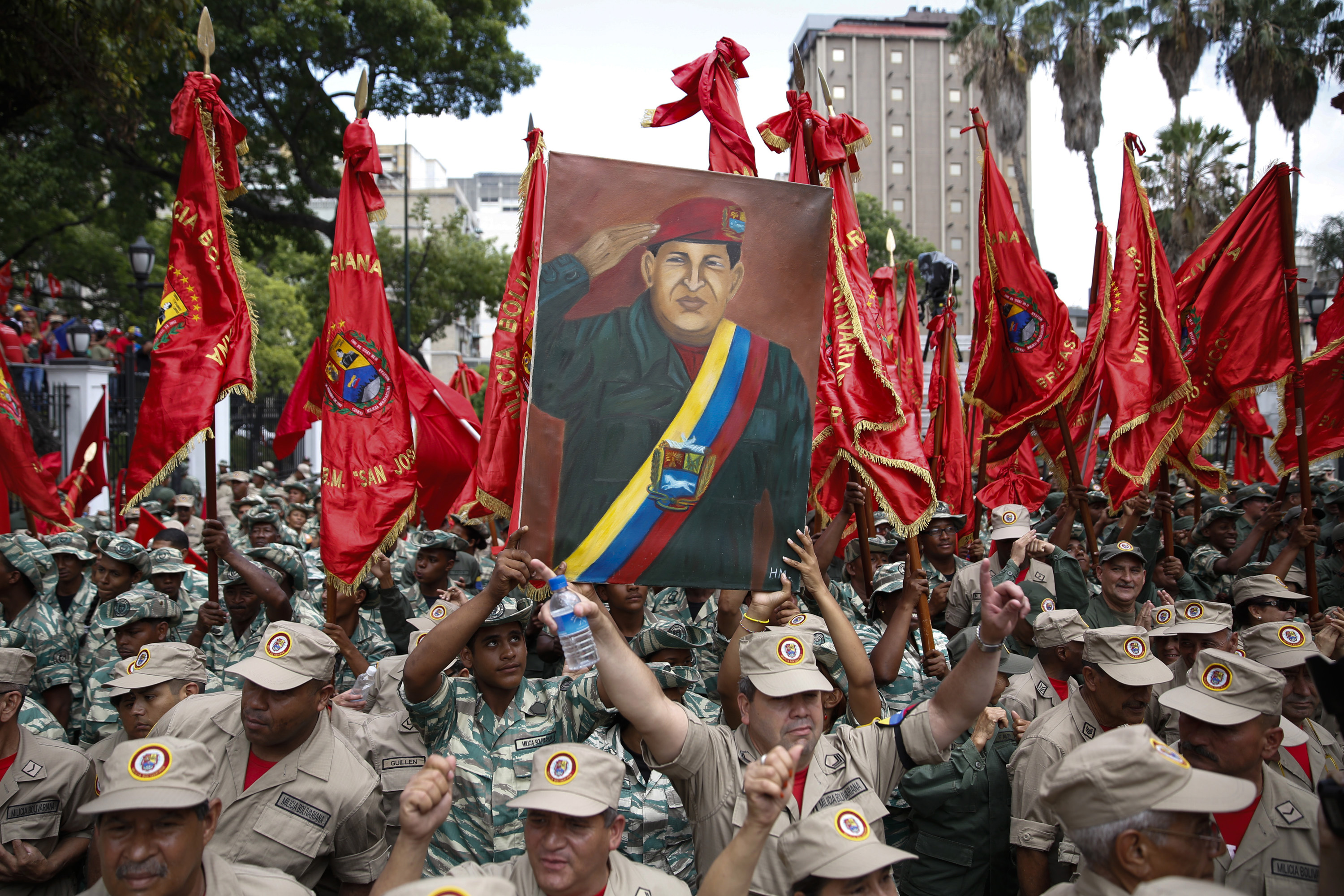 Militia members hold a painting of late Venezuelan President Hugo Chavez during a ceremony in Caracas