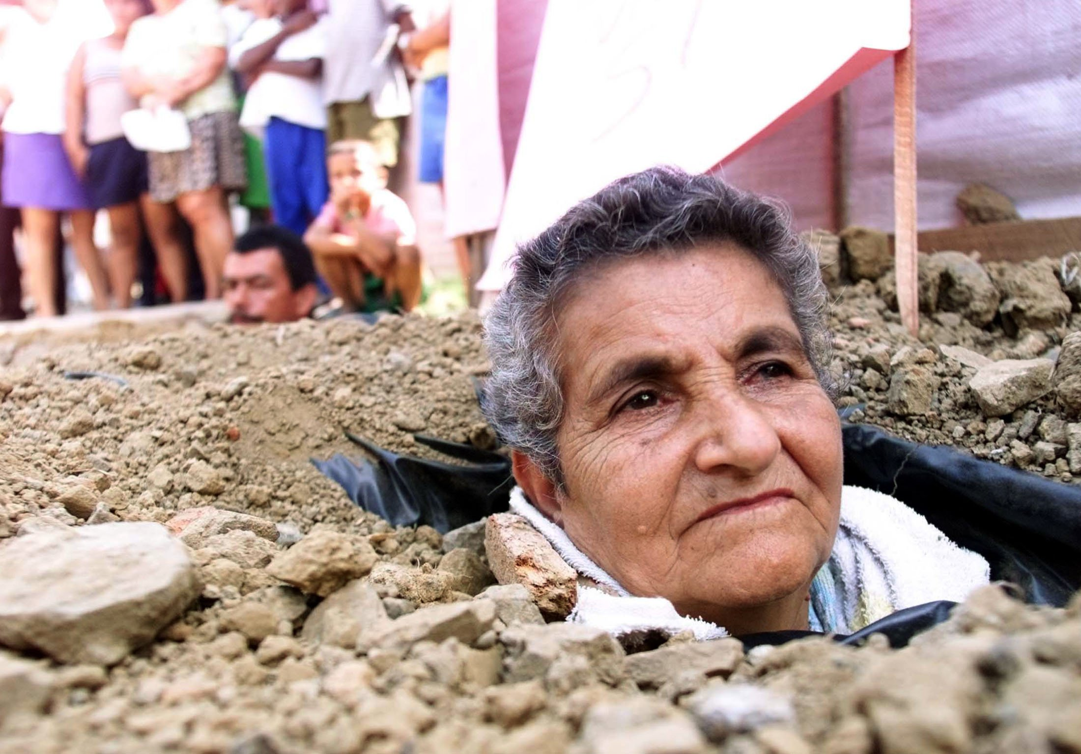 Colombian Maria Gabriela Ruiz, 66, and Nicolas Salazar, 32, (rear), who are buried up to their necks in the ground, stage a protest in a popular sector of Cali, July 4, 2003. Three people, two men and a woman, buried themselves three days ago in protest against the government because 150 displaced persons have not been relocated to a safe sector of Cali. REUTERS/Eduardo Munoz Pictures of the month July 2003