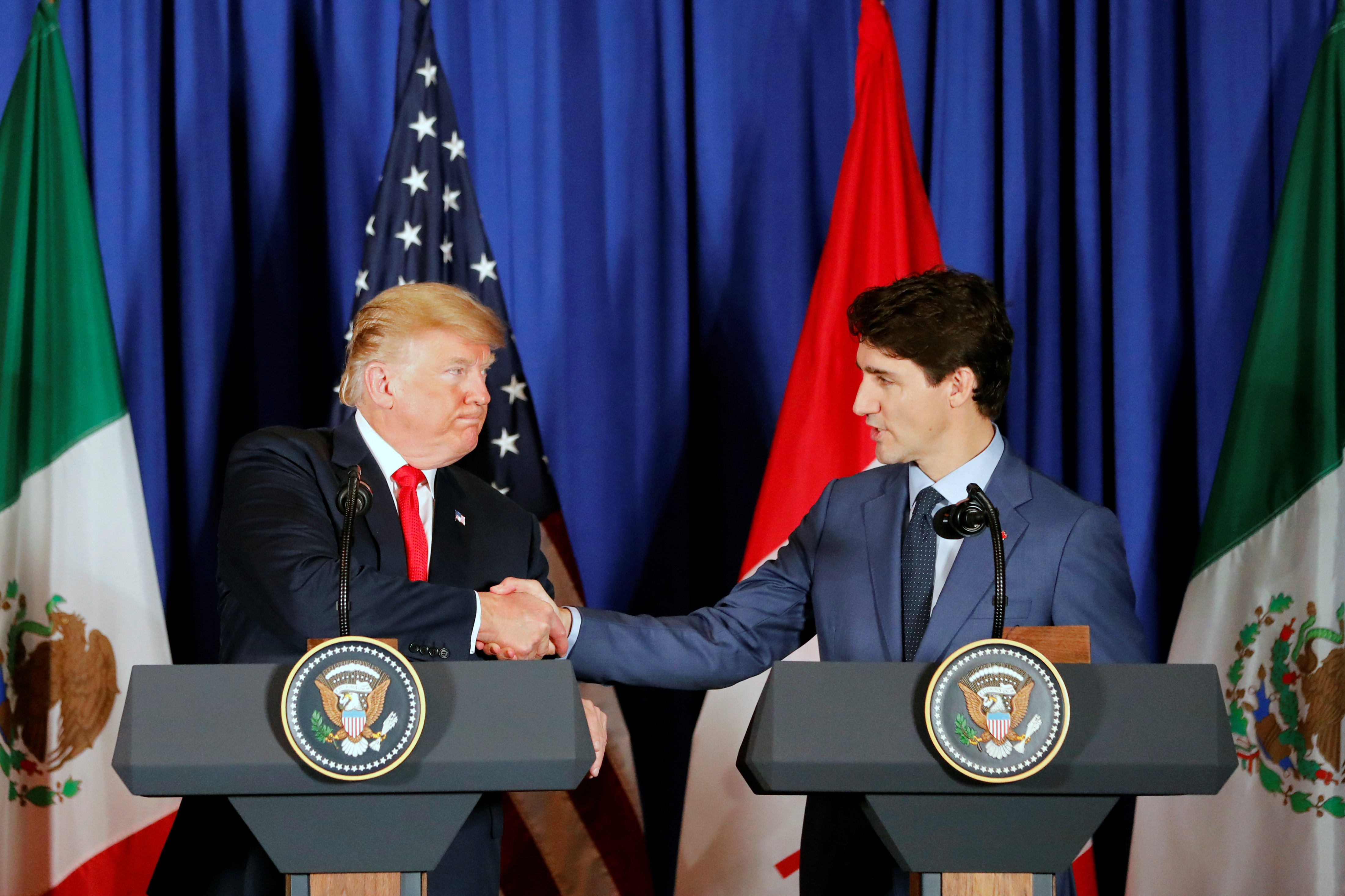U.S. President Donald Trump shake hand with Canada's Prime Minister Justin Trudeau as they attend the USMCA signing ceremony together with Mexico's President Enrique Pena Nieto before the G20 leaders summit in Buenos Aires, Argentina November 30, 2018. REUTERS/Andres Stapff