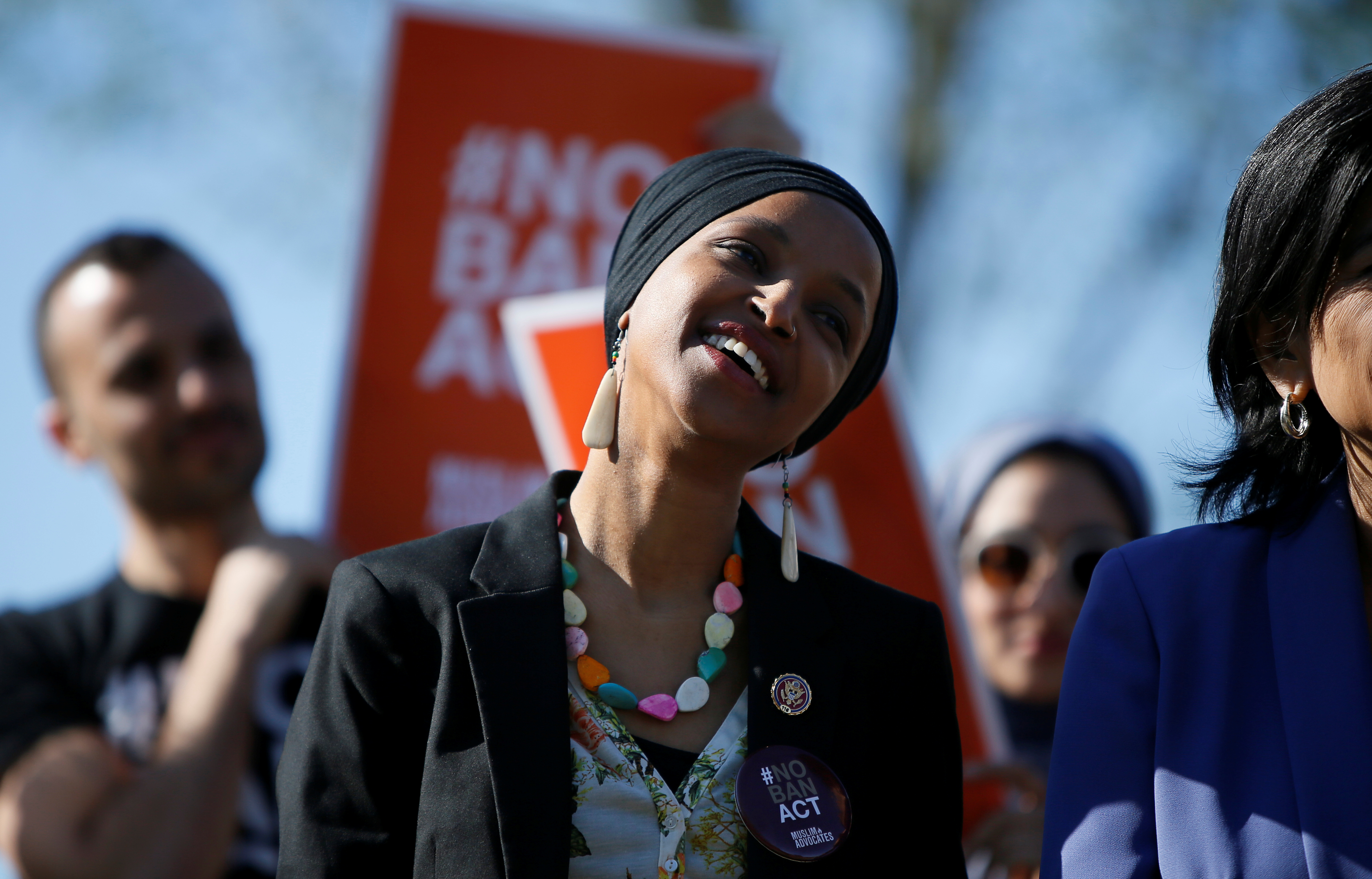 """Rep. Ilhan Omar (D-MN) smiles during a news conference by members of the U.S. Congress """"to announce legislation to repeal President Trump's existing executive order blocking travel from majority Muslim countries"""" outside the U.S. Capitol in Washington, U.S., April 10, 2019. REUTERS/Jim Bourg"""