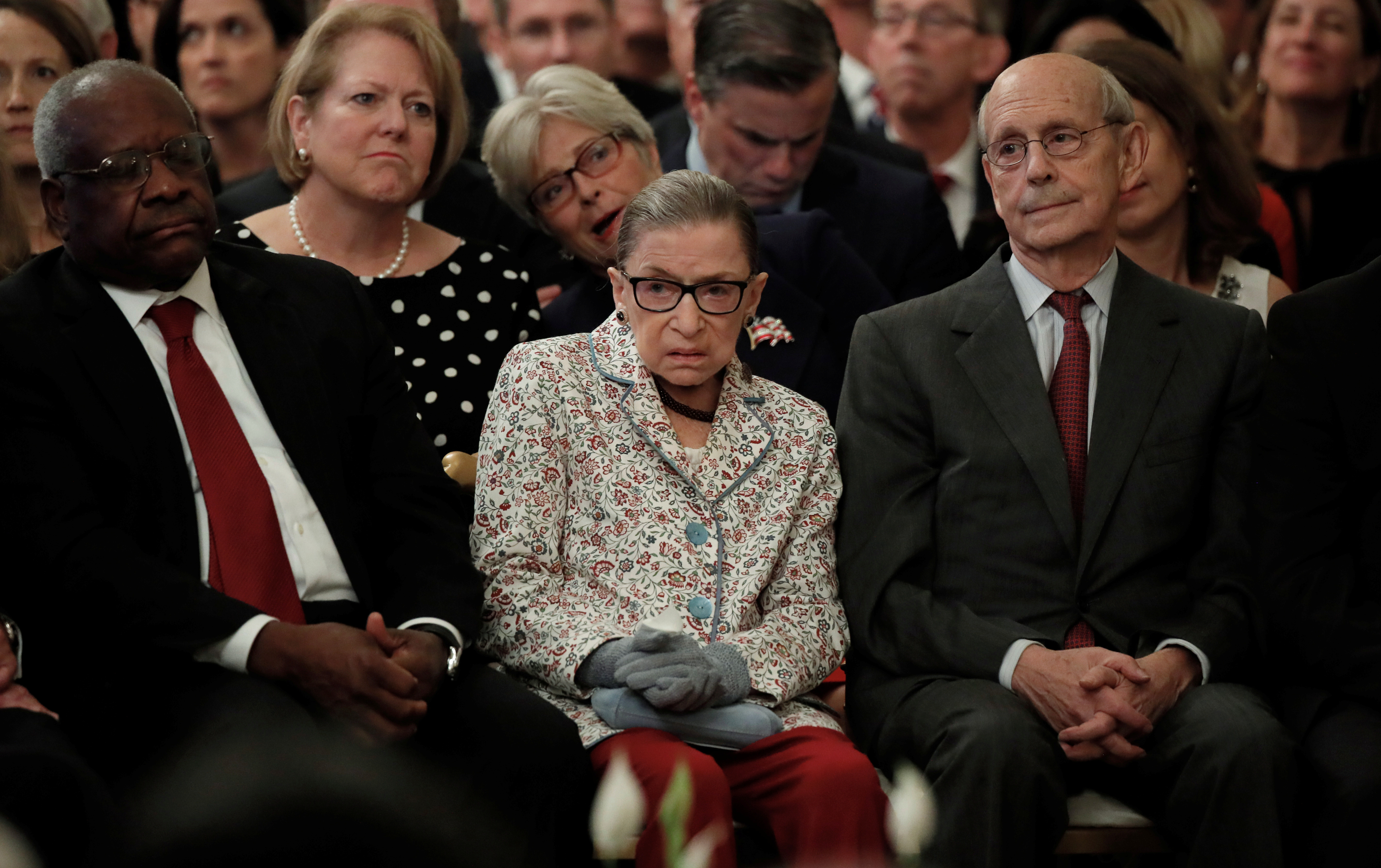 U.S. Supreme Court Associate Justices (L-R) Clarence Thomas, Ruth Bader Ginsburg and Stephen Breyer watch from the front row as Brett Kavanaugh takes his ceremonial oath of office while participating in a ceremonial public swearing-in in the East Room of the White House in Washington, U.S., October 8, 2018. REUTERS/Jim Bourg