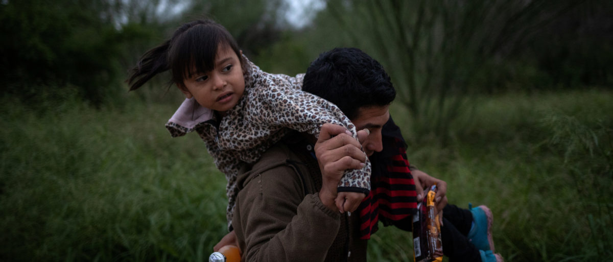 Jose Moreira Deras of Honduras races down a dirt path holding his five year old daughter Crystal after hearing what border patrol agents said was the sound of gunshots where a group of two dozen families members illegally crossed the Rio Grande river into the United States from Mexico, in Fronton, Texas, Oct. 18, 2018. REUTERS/Adrees Latif