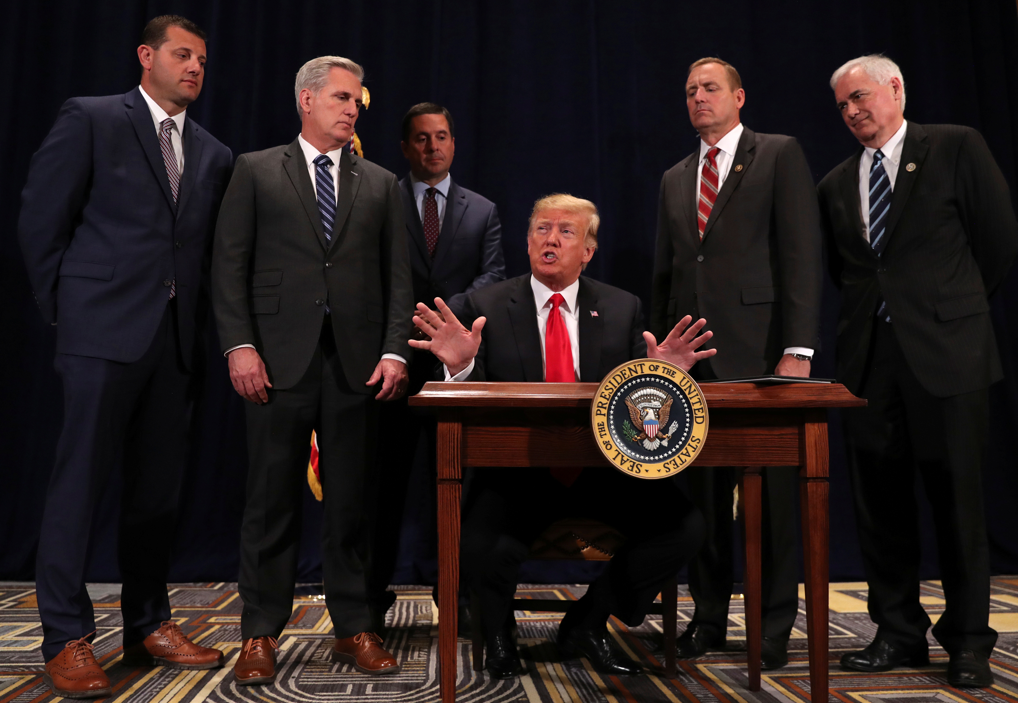 U.S. President Donald Trump, flanked by U.S. Representative David Valadao (R-CA), House Majority Leader Kevin McCarthy (R-CA), Representative Devin Nunes (R-CA), Representative Jeff Denham (R-CA) and Representative Tom McClintock (R-CA), speaks to reporters after signing a presidential memorandum focused on sending more water to farmers in California's Central Valley, at a conference center in Scottsdale, Arizona, U.S., October 19, 2018. REUTERS/Jonathan Ernst