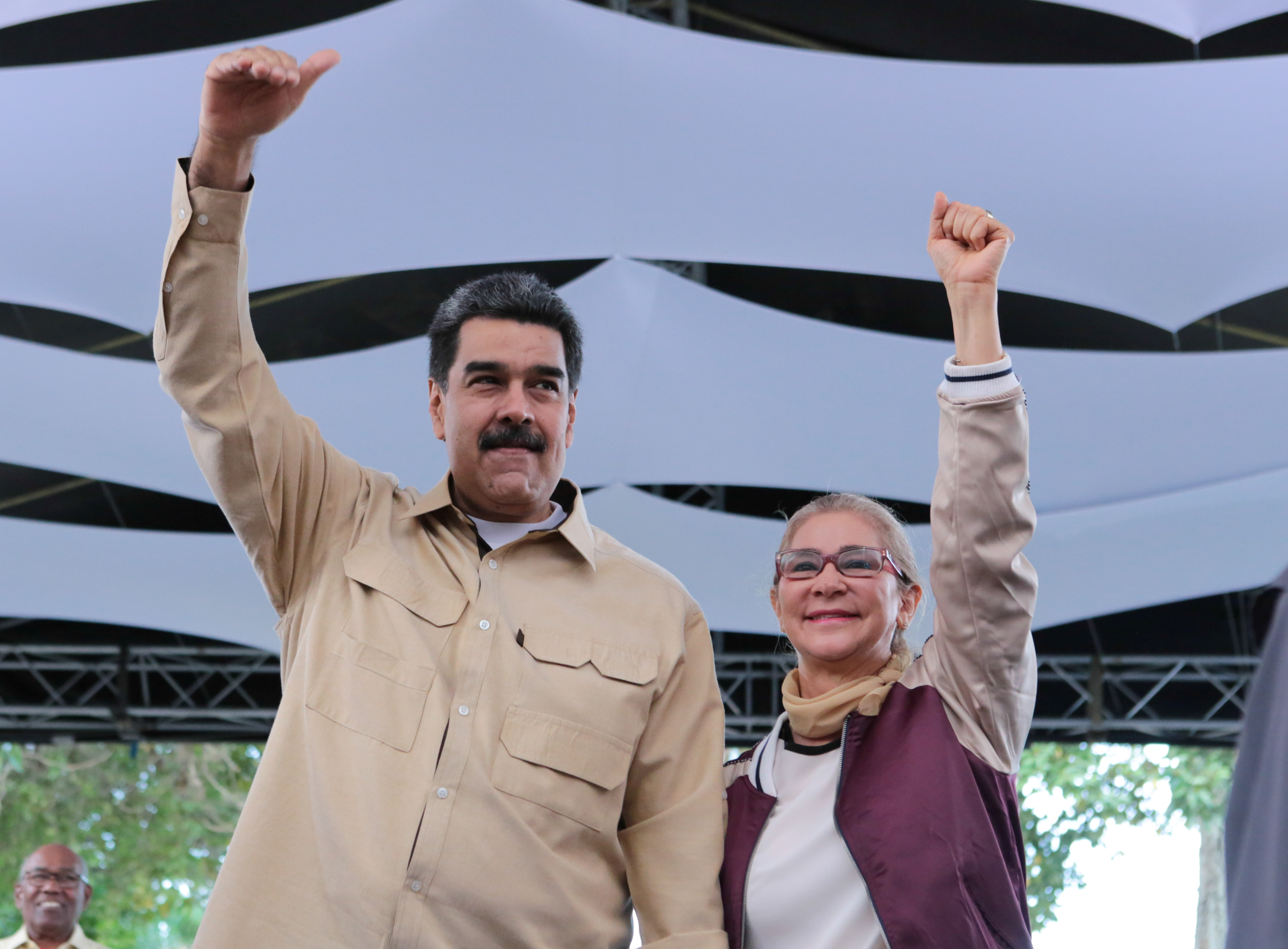 Venezuela's President Nicolas Maduro and his wife Cilia Flores gesture during a meeting with youths in Caracas