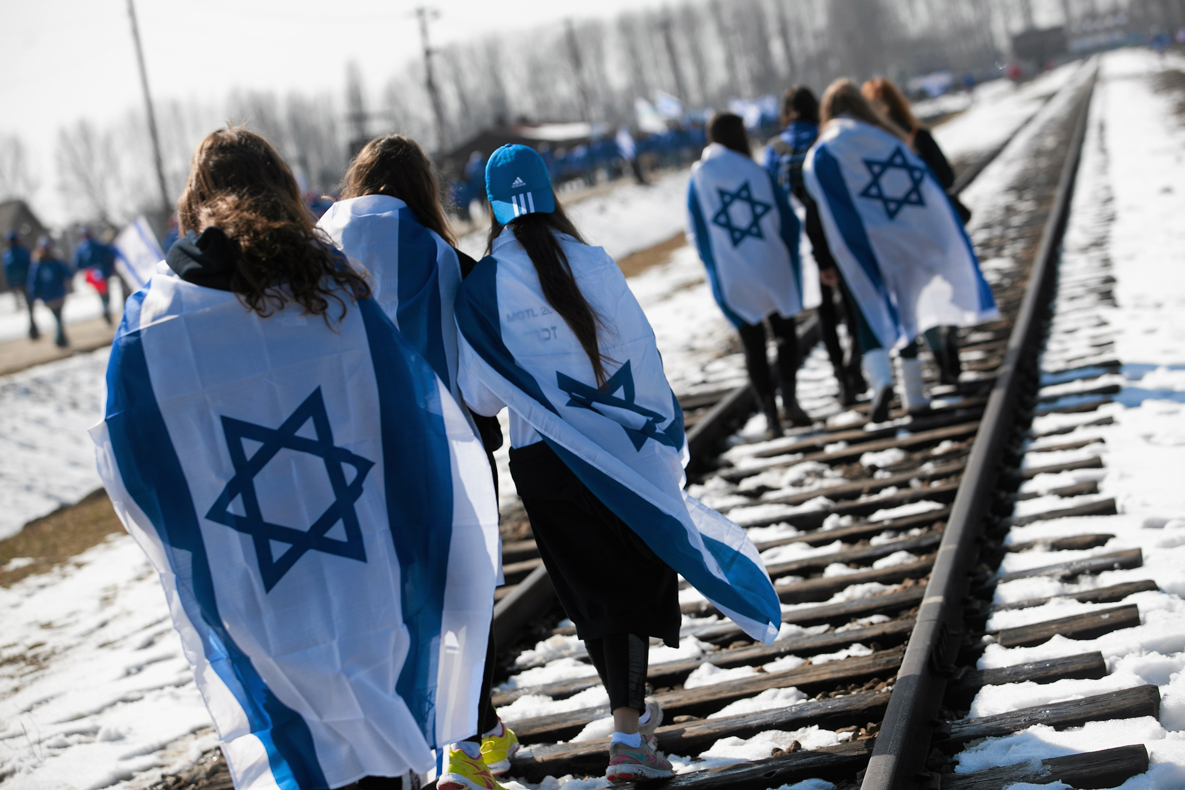 "People wear Israeli flags around their shoulders as they walk on the railroad tracks inside the former Nazi death camp of Birkenau (Auschwitz II) in Oswiecim-Brzezinka, southern Poland April 8, 2013. Thousands of mainly Jewish people participated in the 22nd annual ""March of the Living"", a Holocaust commemoration. REUTERS/Jakub Ociepa/Agencja Gazeta"
