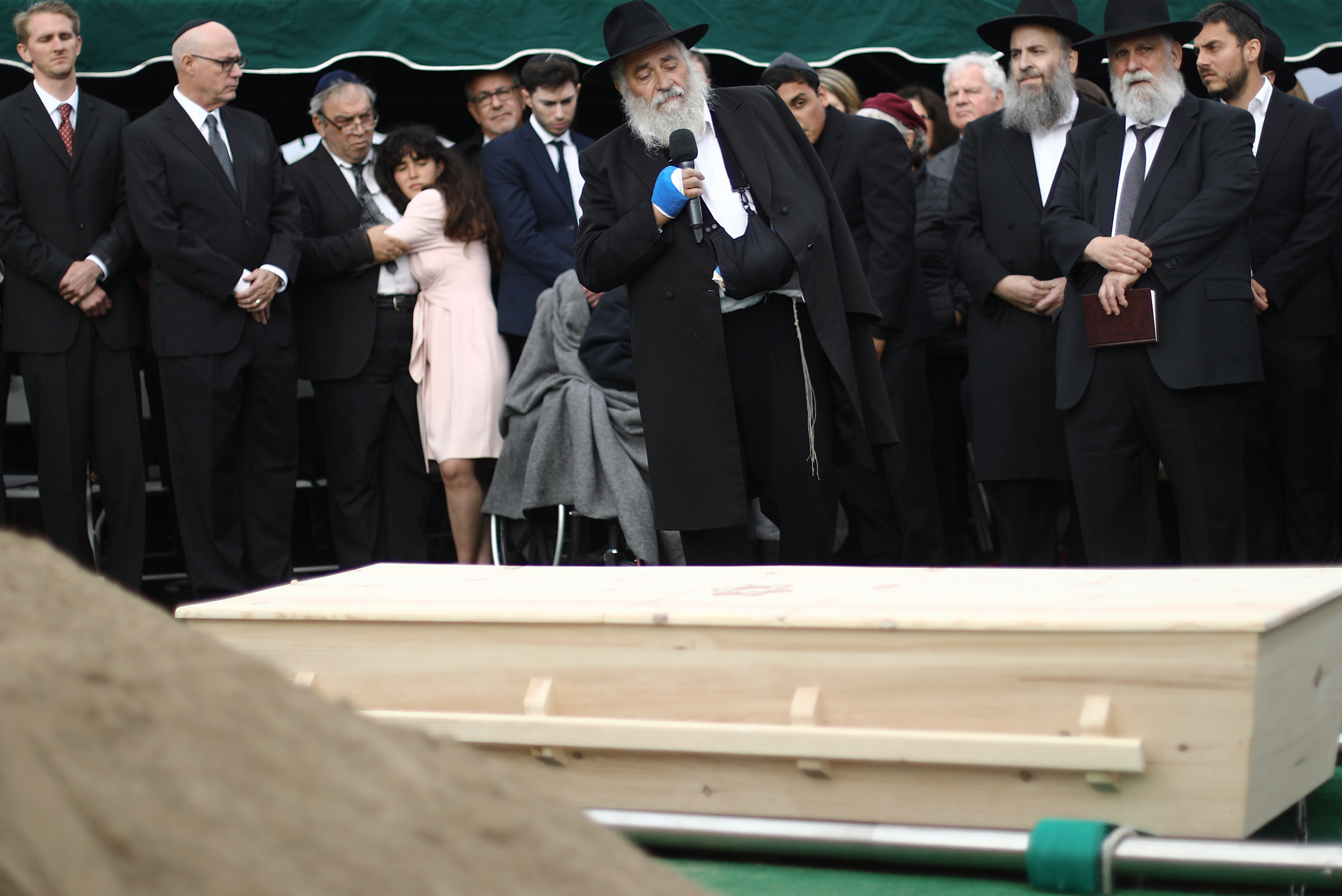 SAN DIEGO, CALIFORNIA - APRIL 29: Hannah Kaye (LEFT CENTER), daughter of shooting victim Lori Gilbert Kaye, is held by her father Howard Kaye as wounded Rabbi Yisroel Goldstein (CENTER) speaks above the casket during a graveside service on April 29, 2019 in San Diego, California. (Photo by Mario Tama/Getty Images)
