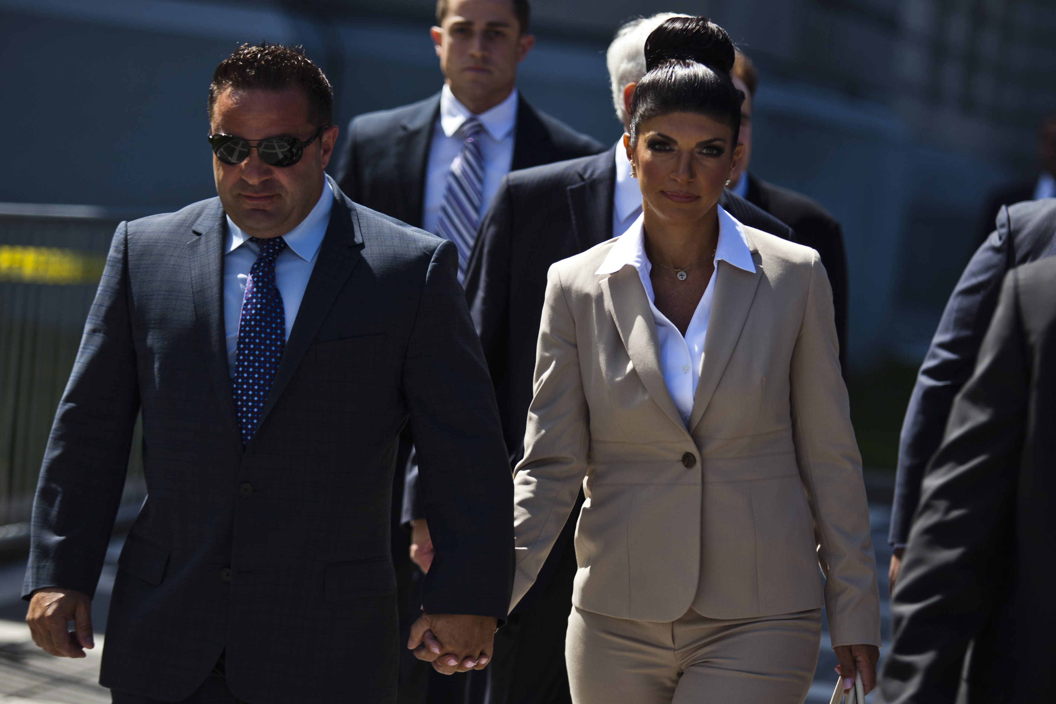 "Teresa Giudice and her husband Giuseppe ""Joe"" Giudice hold hands as they leave the federal court in Newark, New Jersey"