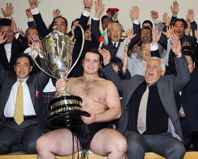 Bulgaria's sumo wrestler Kotooshu (C), whose real name is Kaloyan Stefanov Mahlyanov, poses with his trophy after winning the Emperor's Cup Grand Sumo Tournament in Tokyo May 25, 2008. Bulgaria's Kotooshu became the first European to win a prestigious Emperor's Cup when he won the Summer Grand Sumo Tournament. REUTERS/Kyodo (JAPAN).
