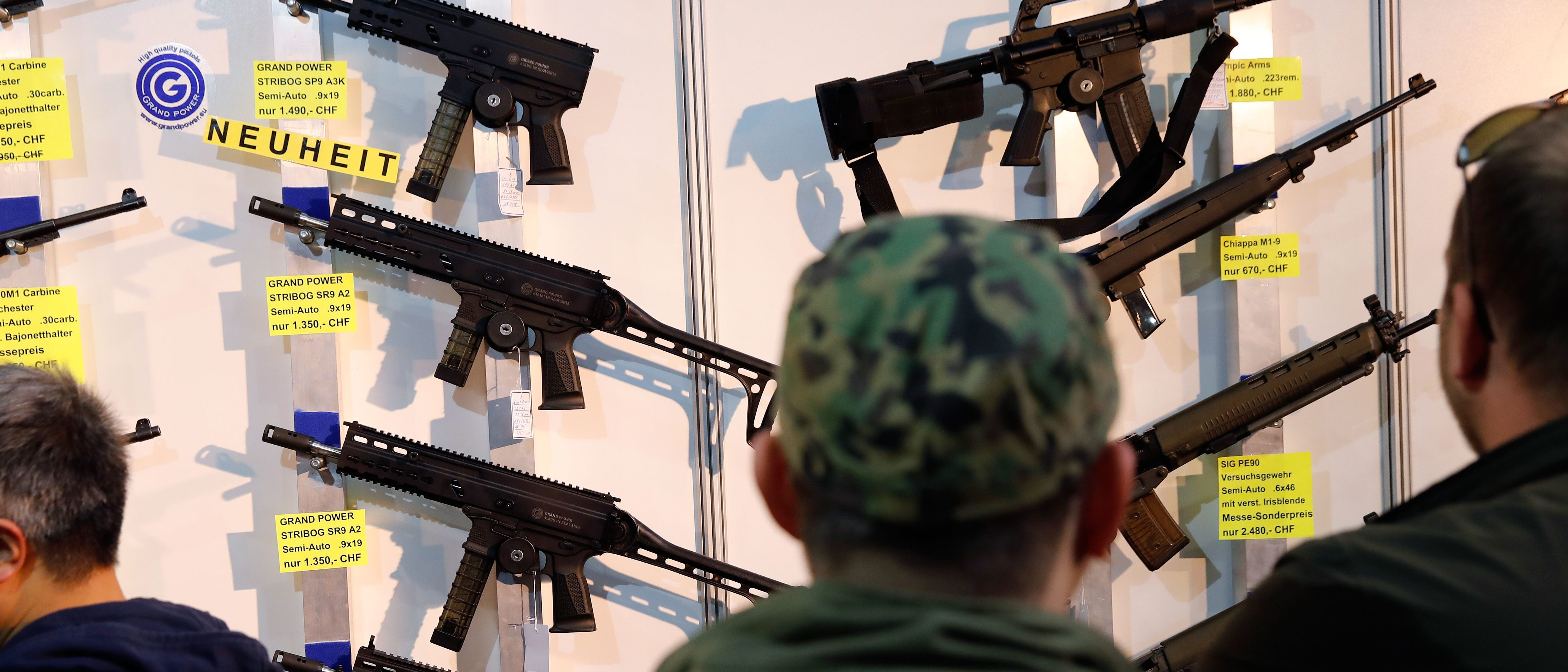 Visitors look at semi-automatic shotguns displayed on a wall during the 45th edition of the Arms Trade Fair, in Lucerne, on March 29, 2019. - Switzerland, where gun culture has deep roots, has managed to avoid the charged national debates surrounding firearm ownership that have consumed other countries. But in a country where compulsory military service means that many are comfortable around weapons, voters might, in a May 2019 referendum, push back against gun reforms demanded by the European Union. (Photo by STEFAN WERMUTH/AFP/Getty Images)