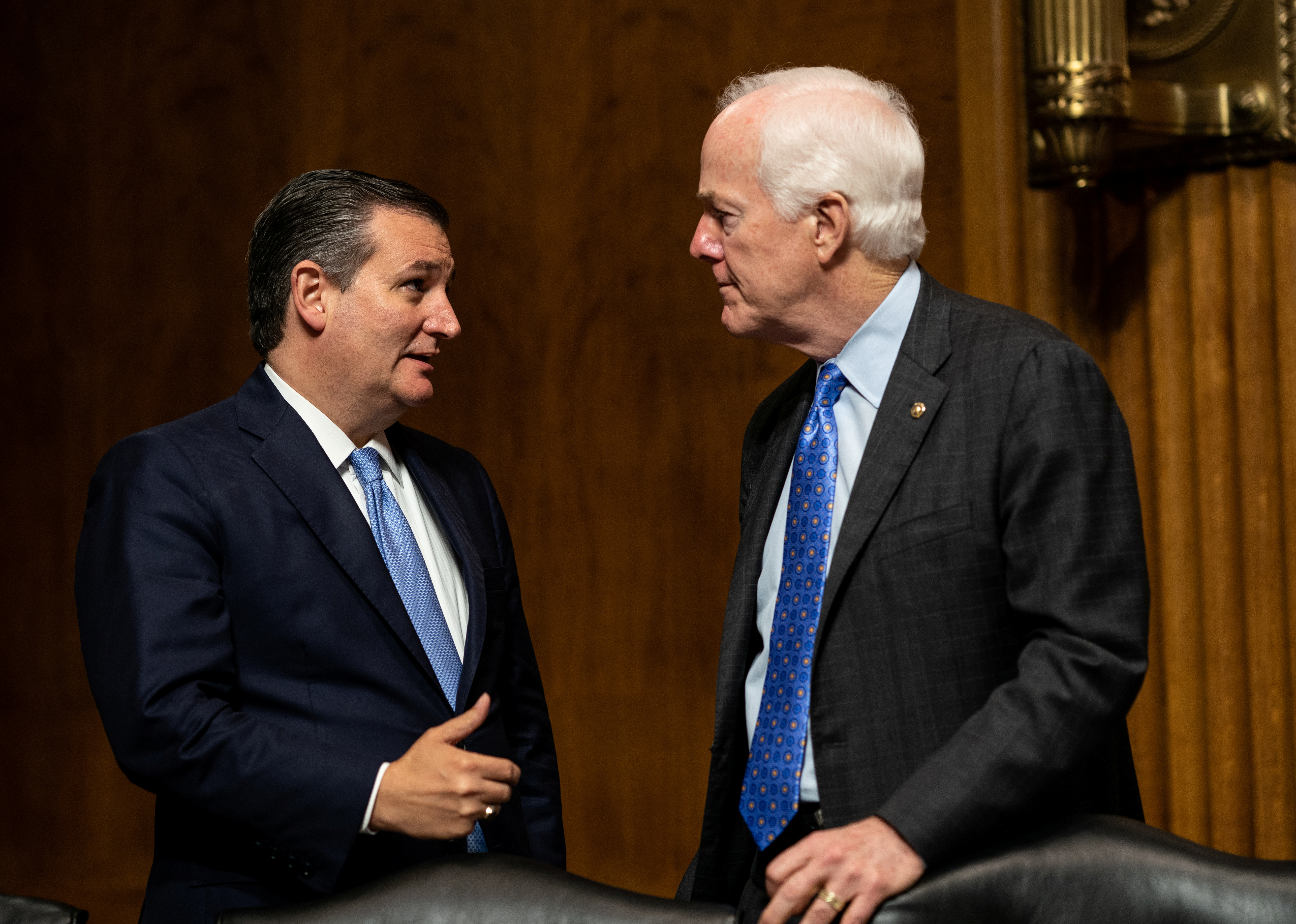 Senators Ted Cruz, left, and John Cornyn talk as Judge Brett Kavanaugh testifies in front of the Senate Judiciary committee regarding sexual assault allegations at the Dirksen Senate Office Building on Capitol Hill in Washington, U.S., September 27, 2018. Erin Schaff/Pool via REUTERS