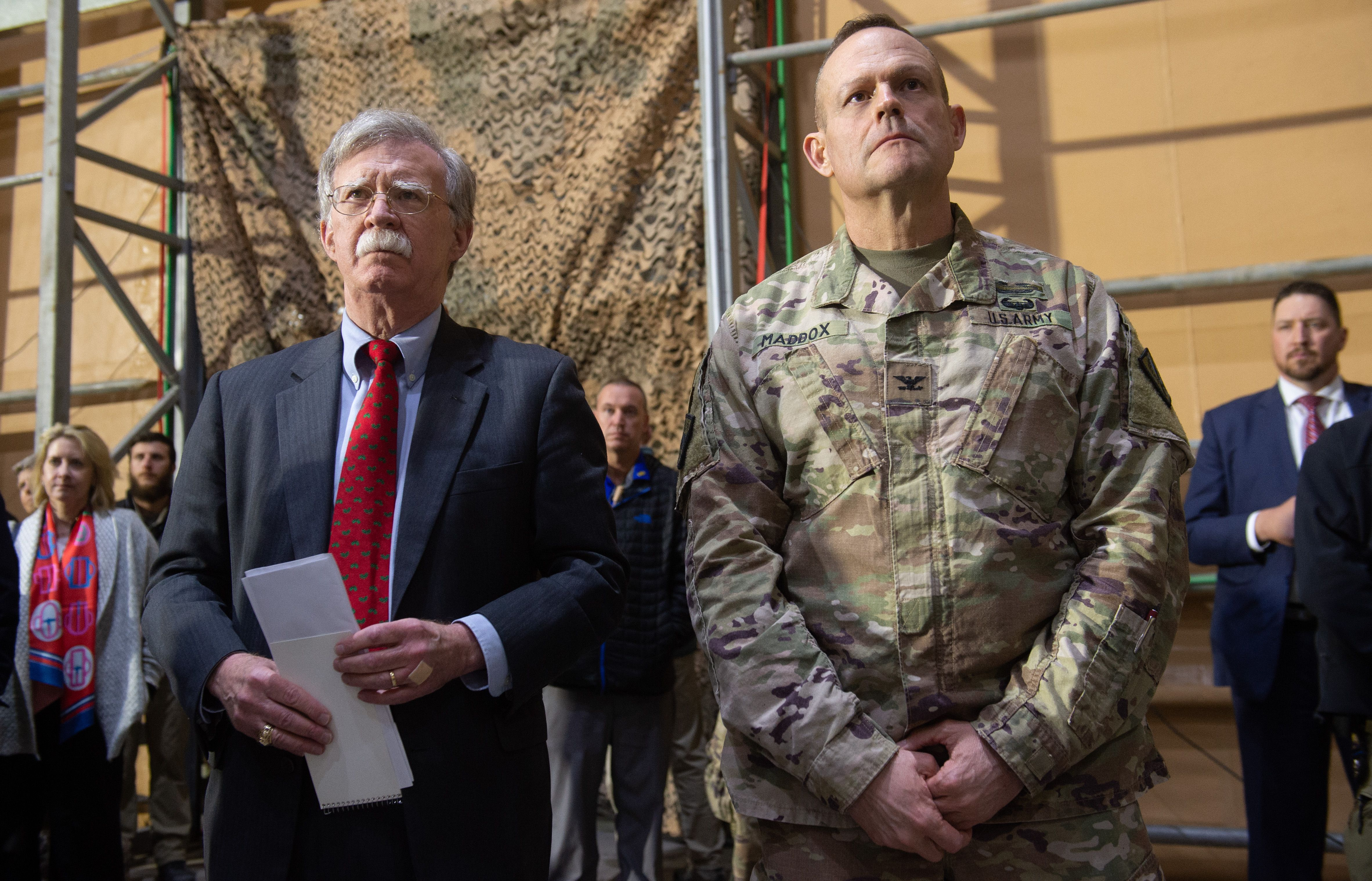 US National Security Adviser John Bolton (L) listens as US President Donald Trump speaks to members of the US military during an unannounced trip to Al Asad Air Base in Iraq on December 26, 2018. - President Donald Trump arrived in Iraq on his first visit to US troops deployed in a war zone since his election two years ago. SAUL LOEB/AFP/Getty Images