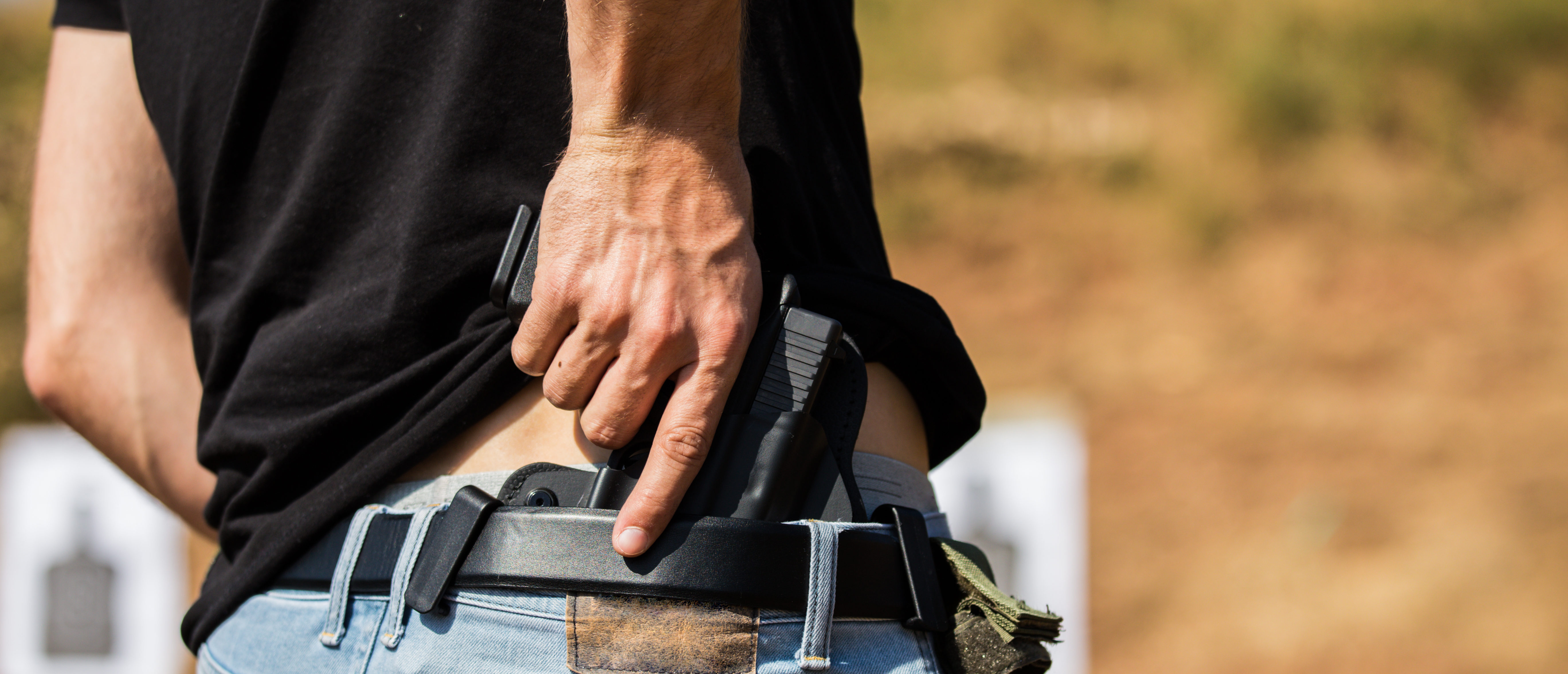 A handgun is drawn from a concealed carry holster. Photo by Shutterstock.