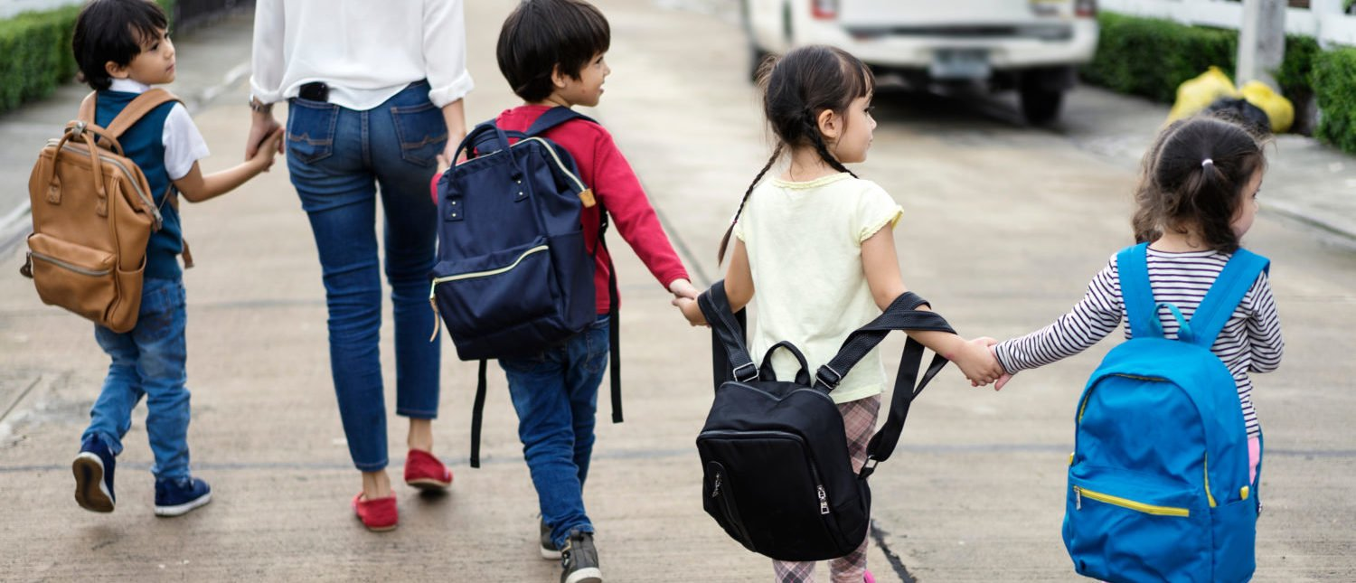 Mom and four kids holding hands, carrying schoolbags, walking to school. [Shutterstock - iseeu2]