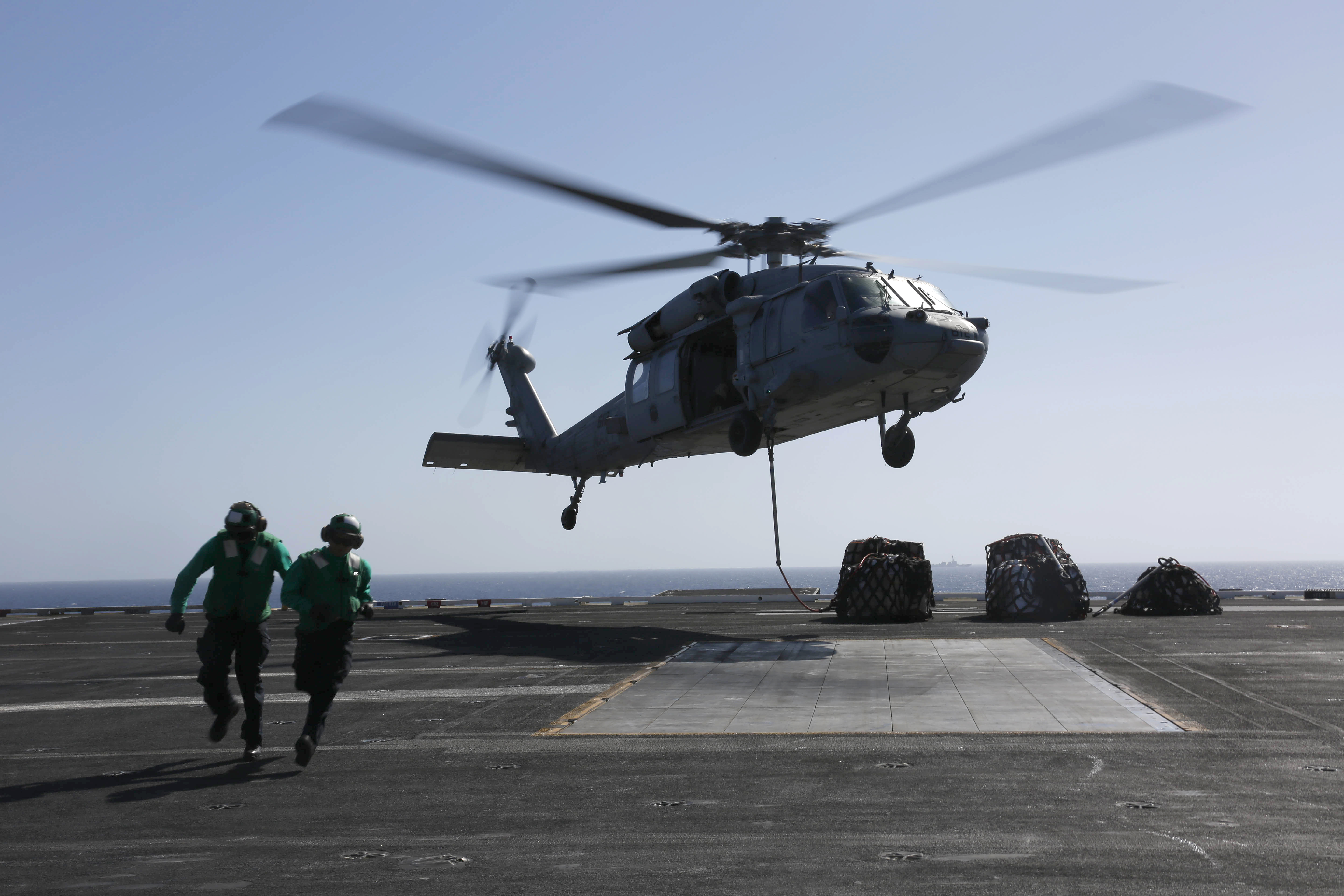 "In this handout photo provided by the U.S. Navy, Logistics Specialist 1st Class Ousseinou Kaba (left), from Silver Spring, Md., and Logistics Specialist Seaman Abigail Marshke, from Flint, Mich., attach cargo to an MH-60S Sea Hawk helicopter from the ""Nightdippers"" of Helicopter Sea Combat Squadron (HSC) 5 from the flight deck of the Nimitz-class aircraft carrier USS Abraham Lincoln (CVN 72) May 10, 2019 in the Red Sea. Photo by Mass Communication Specialist Mass Communication Specialist 3rd Class Amber Smalley/U.S. Navy via Getty Images"