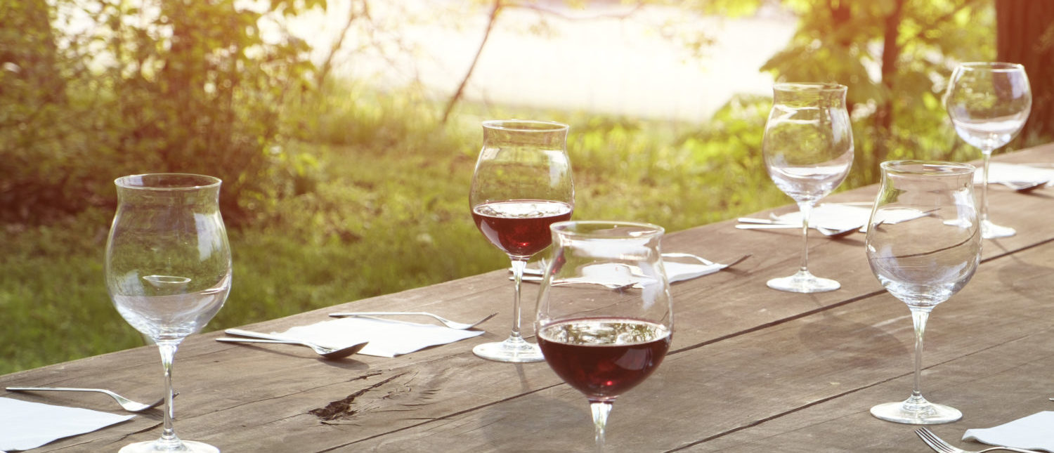 Wine glasses on a wooden table outdoors in the countryside. [Shutterstock - tommaso79]