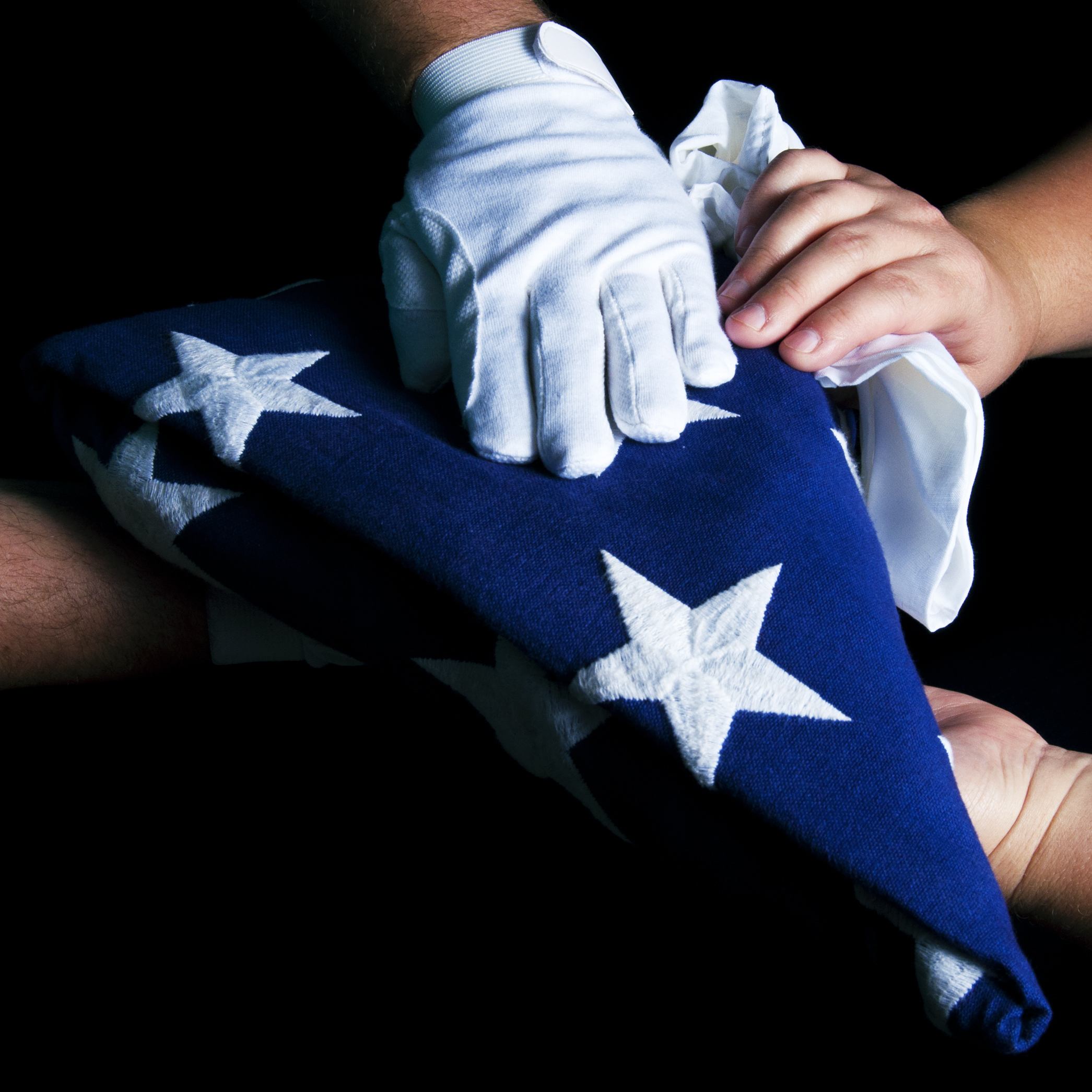 A white gloved hand presents a flag to a woman's hands (Crosby Photo/Shutterstock)
