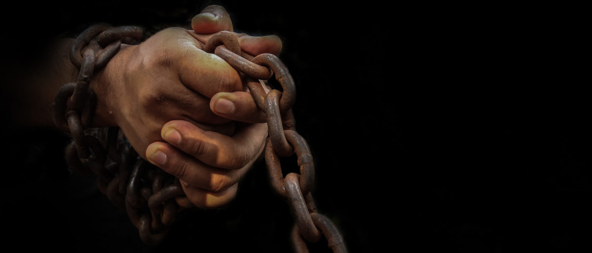 A slave's hands are in chains. Shutterstock image via Sanit Fuangnakhon