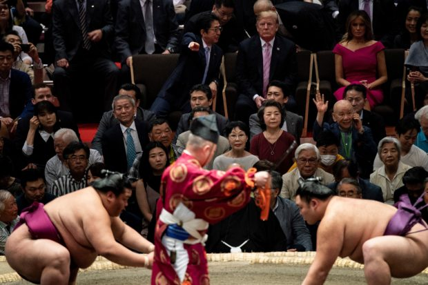 Japan's Prime Minister Shinzo Abe (centre L) speaks to US President Donald Trump (C) as they watch a sumo battle during the Sumer Grand Sumo Tournament at Ryogoku Kokugikan Stadium in Tokyo on May 26, 2019. BRENDAN SMIALOWSKI/AFP/Getty Images