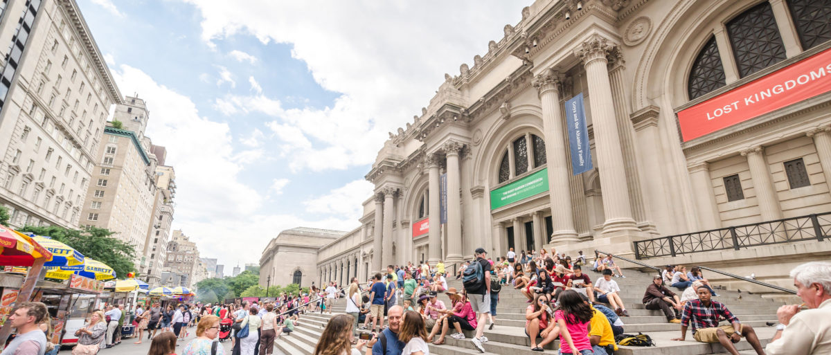 Visitors hang around the steps of The Metropolitan Museum of Art. Shutterstock image via Alexander Prokopenko